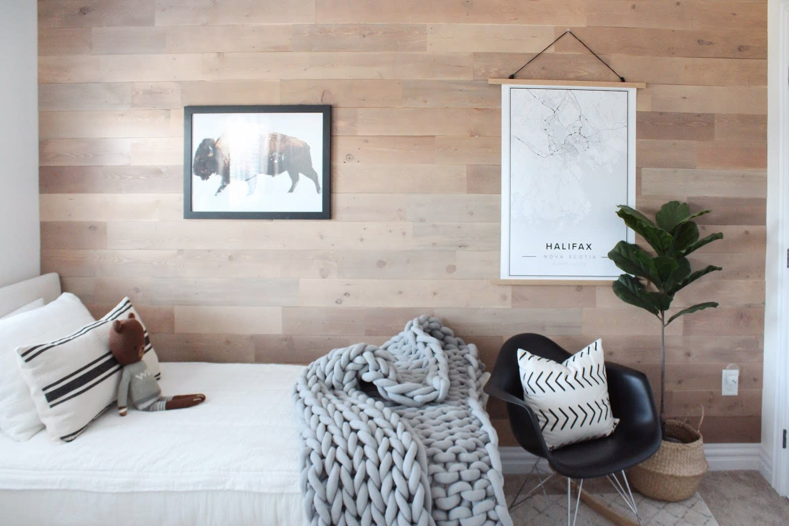 Real wood feature wall made from sand stone finish peel and stick wood planks behind a child's bed.