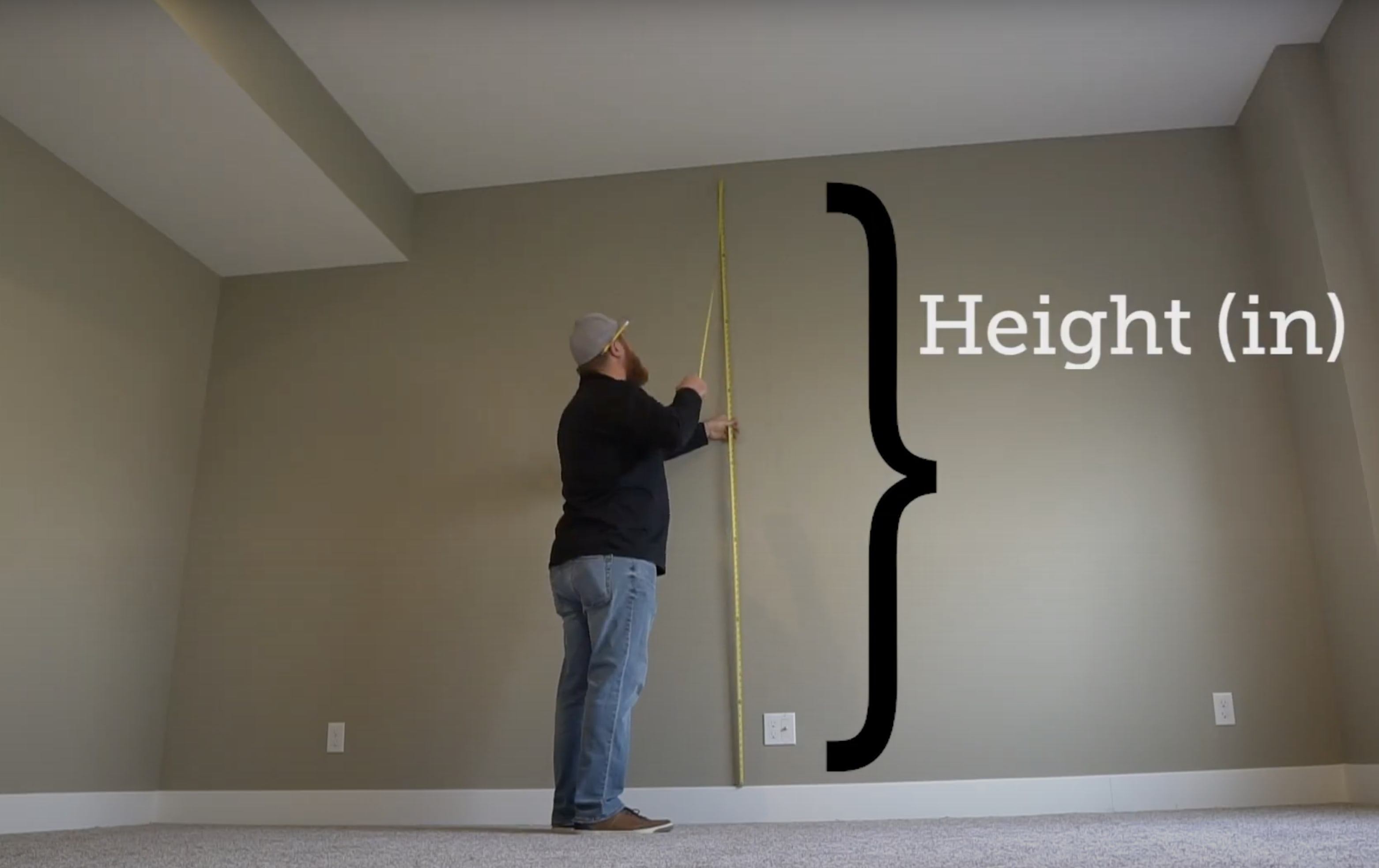 Man using tape measure to determine the area of a wall and how much Stikwood to order.
