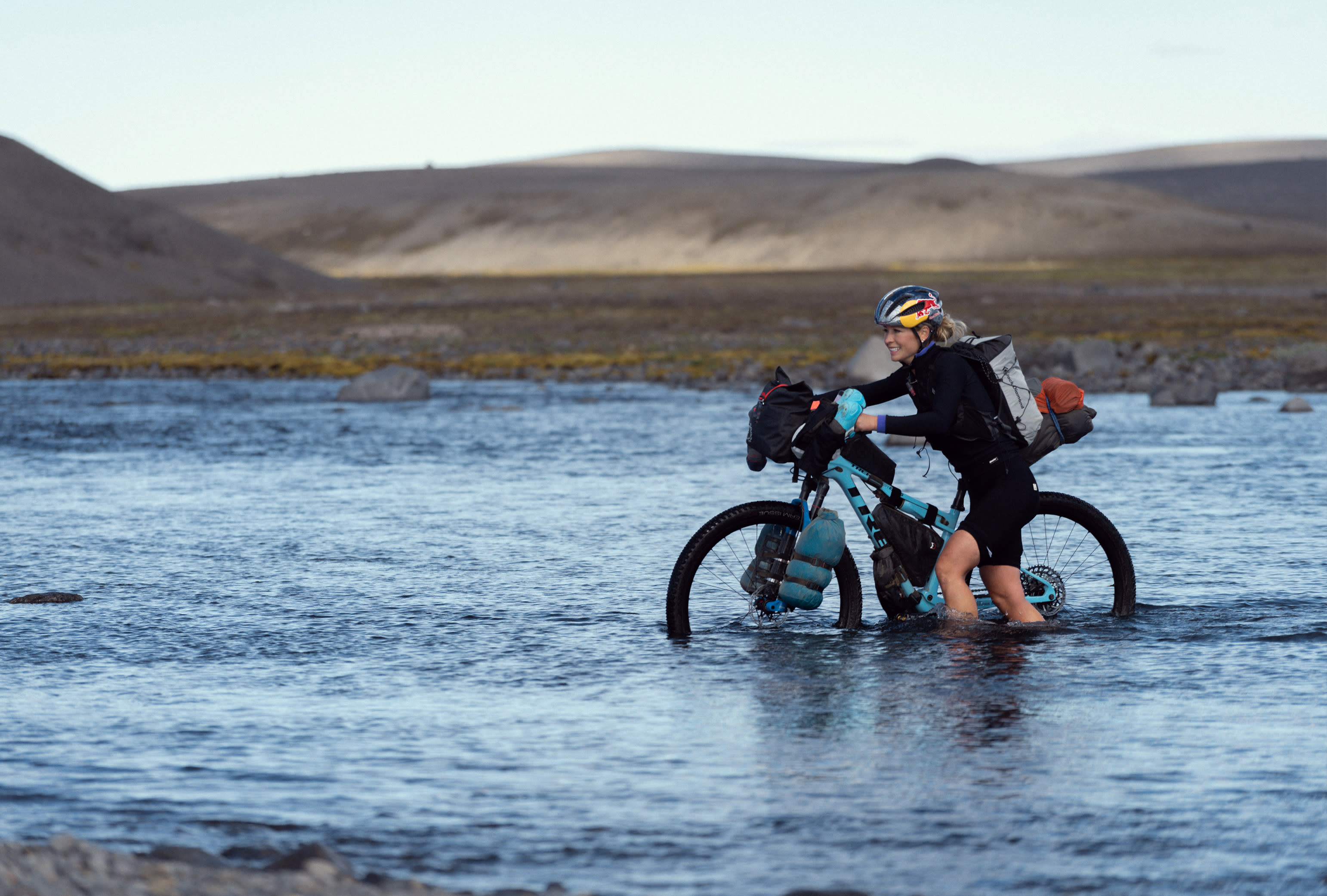 Woman pushing her bike through calf-deep water