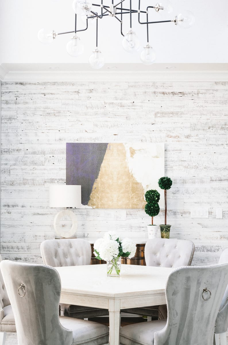 Stikwood reclaimed white wood planks make a perfect backdrop to a modern dining room scene.