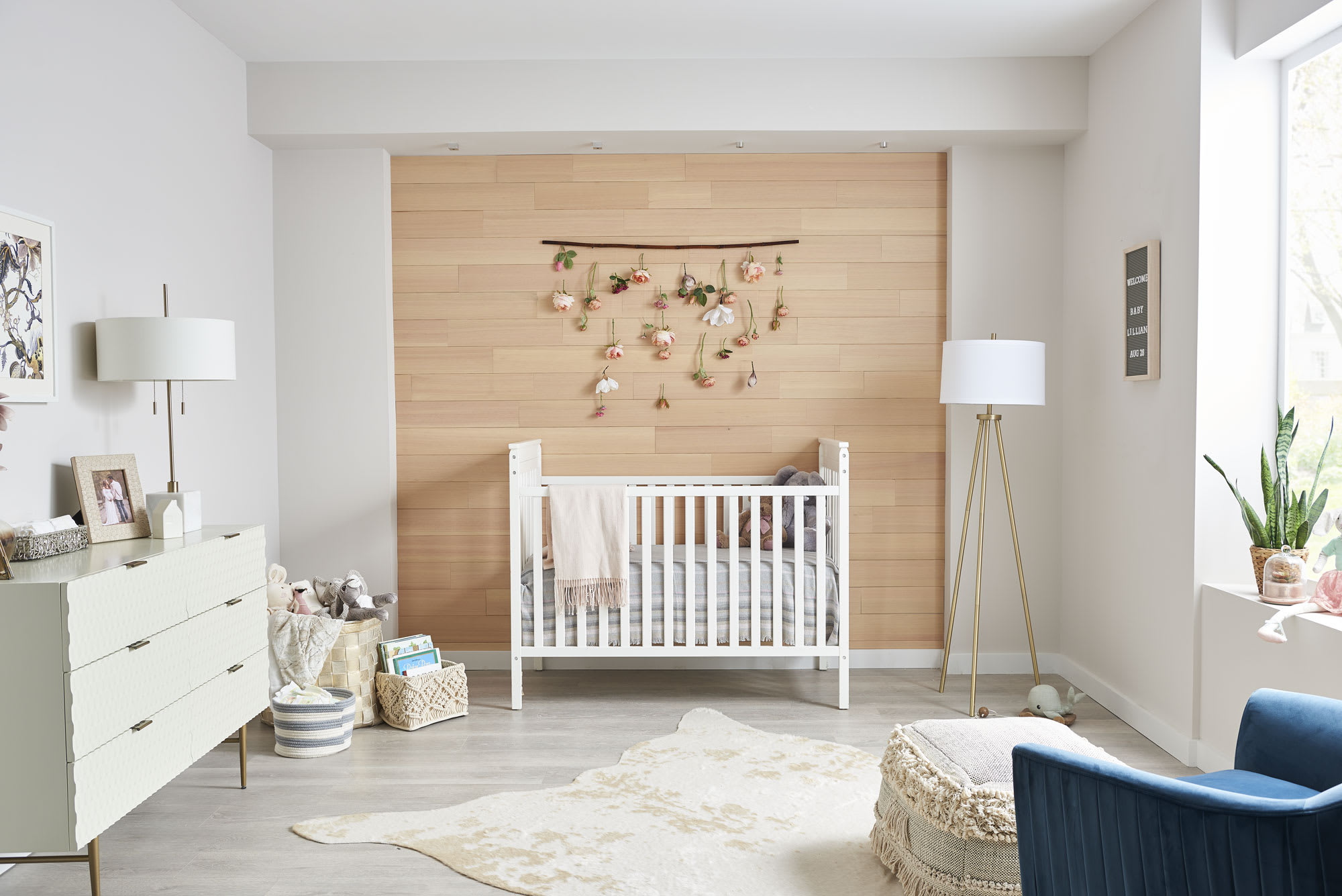 White walls and crib in a nursery with a vertical grain natural peel and stik wood accent wall.