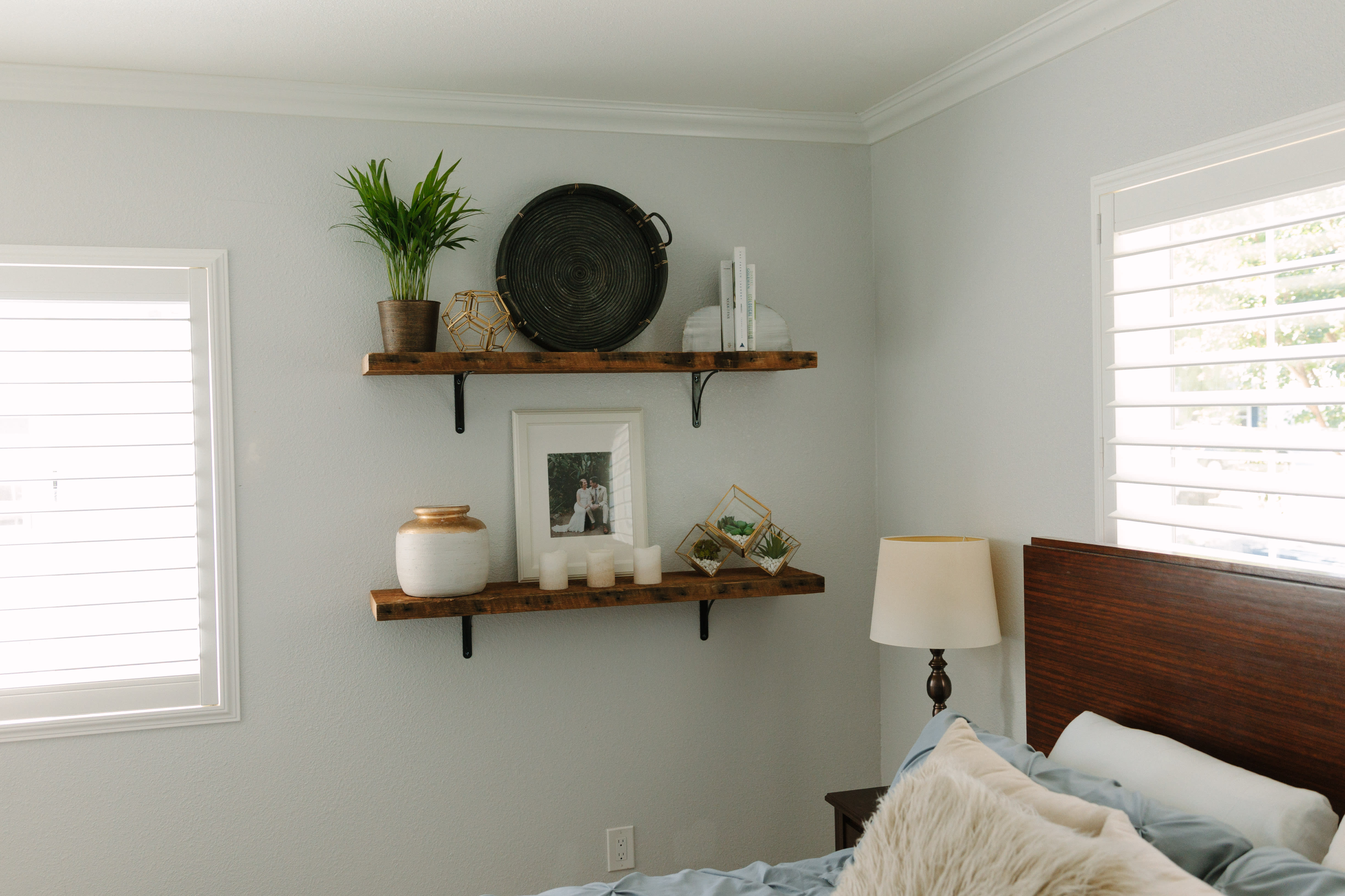 Two decorated reclaimed wood shelves on a bedroom wall.
