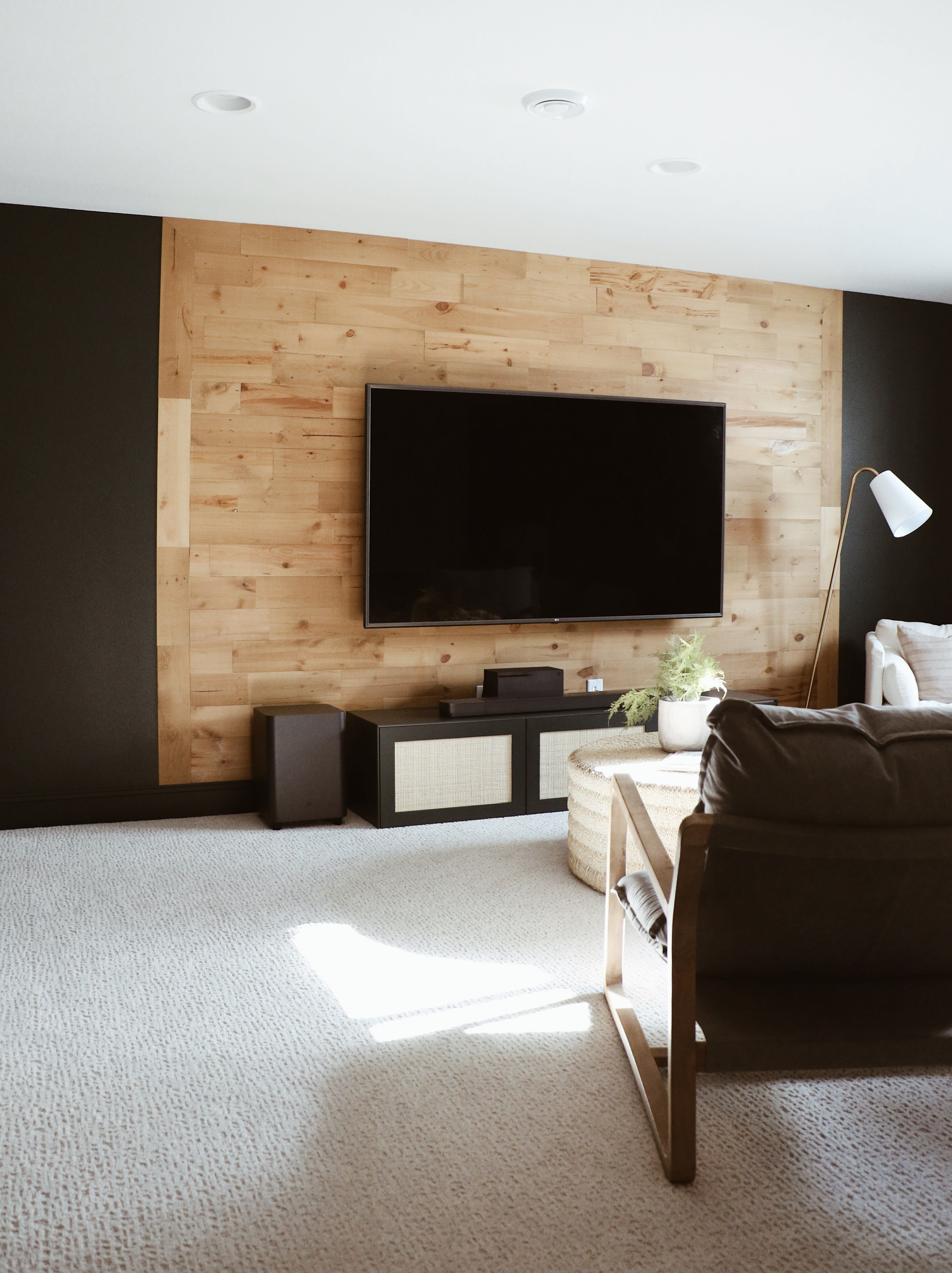 Modern home theater room with a Stikwood Golden Oak peel and stick real reclaimed wood focal wall.