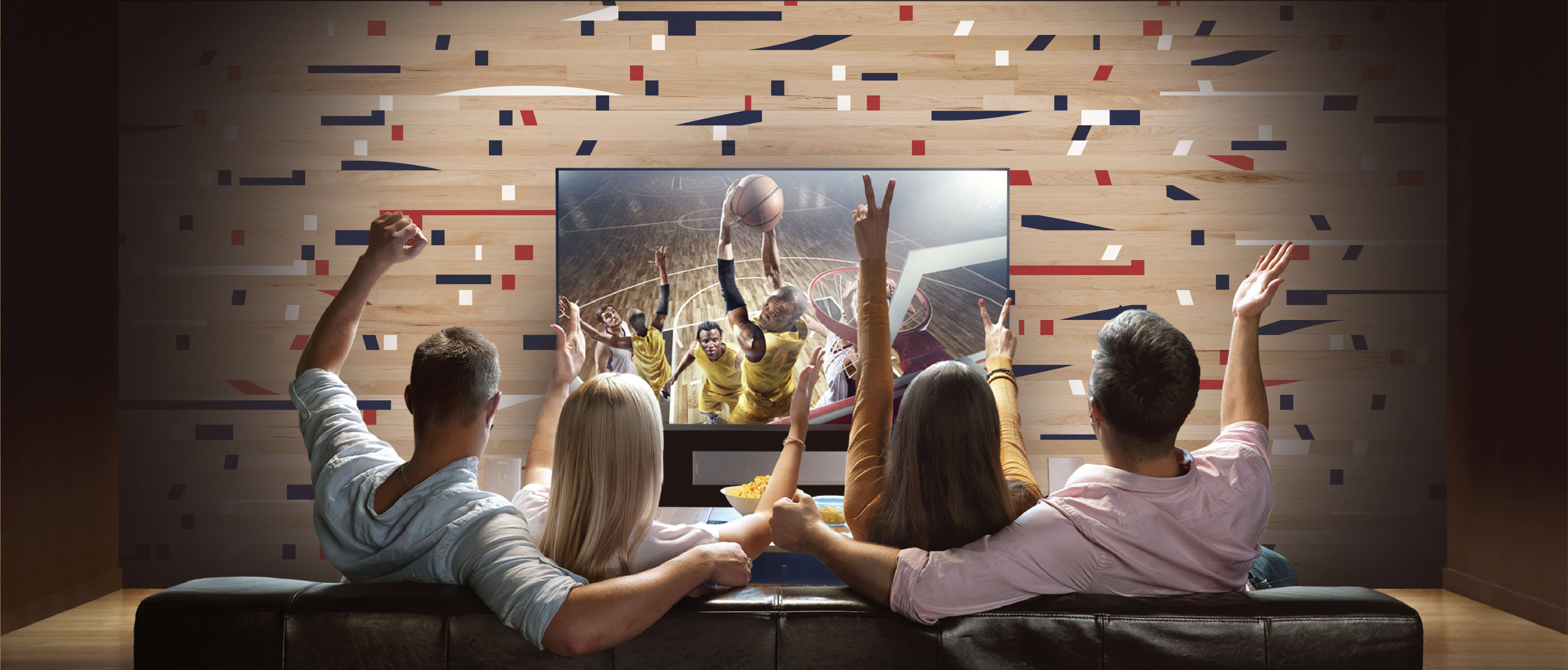 4 fans sitting on a couch watching a basketball game on TV in front of a Stikwood Fanwall peel and stick custom sports wall.