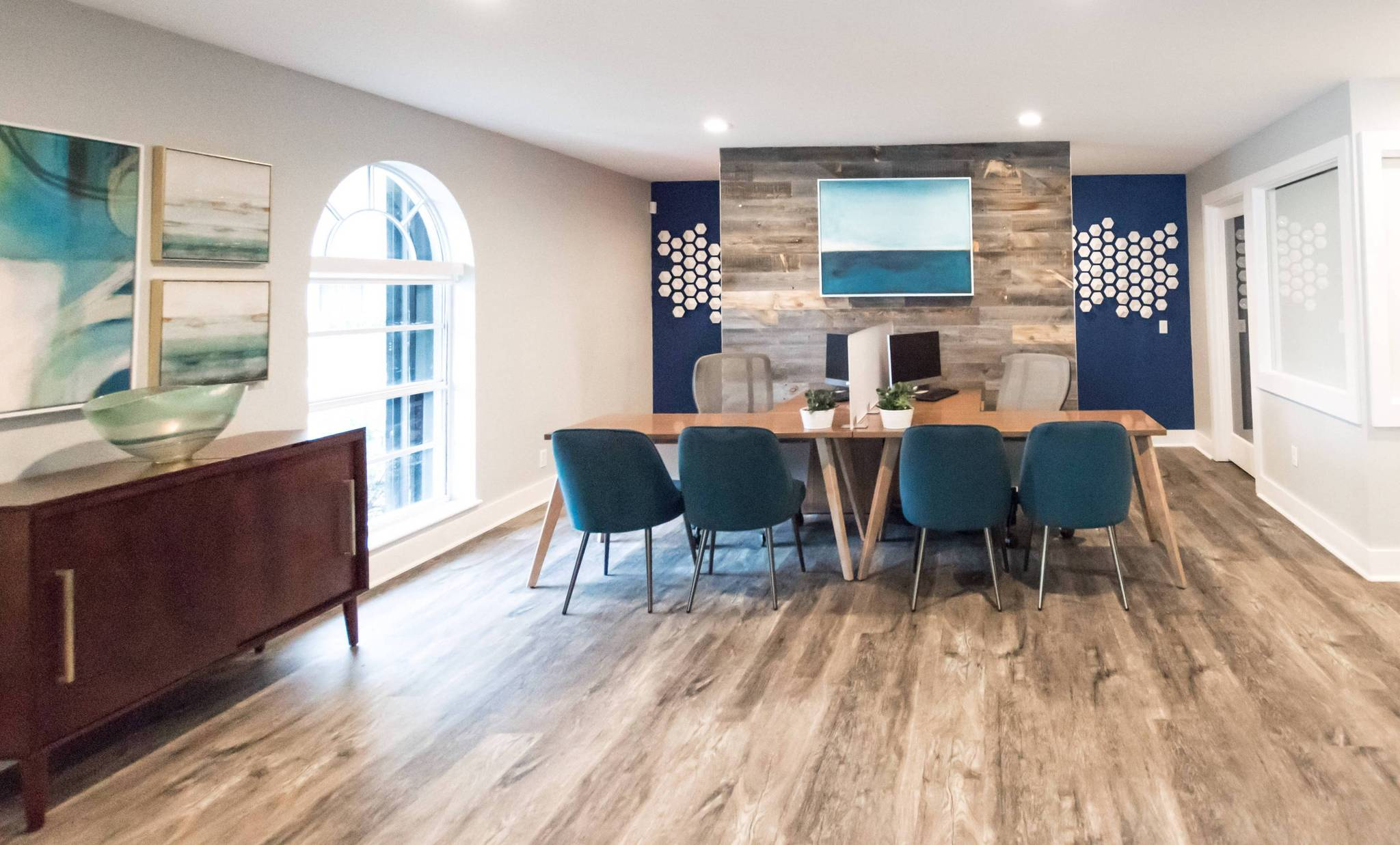 Natalia Chinea Designs created this midcentury modern open office with a Stikwood reclaimed weathered barn wood accent wall.