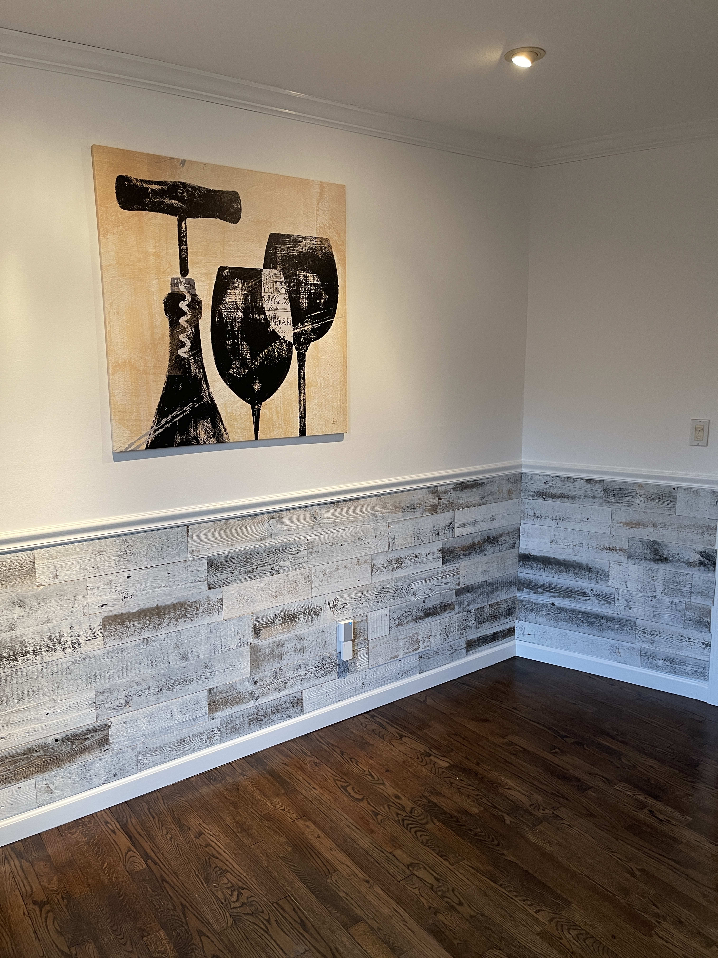 Reclaimed weathered wood white peel and stick wood plank wainscot in dining room.