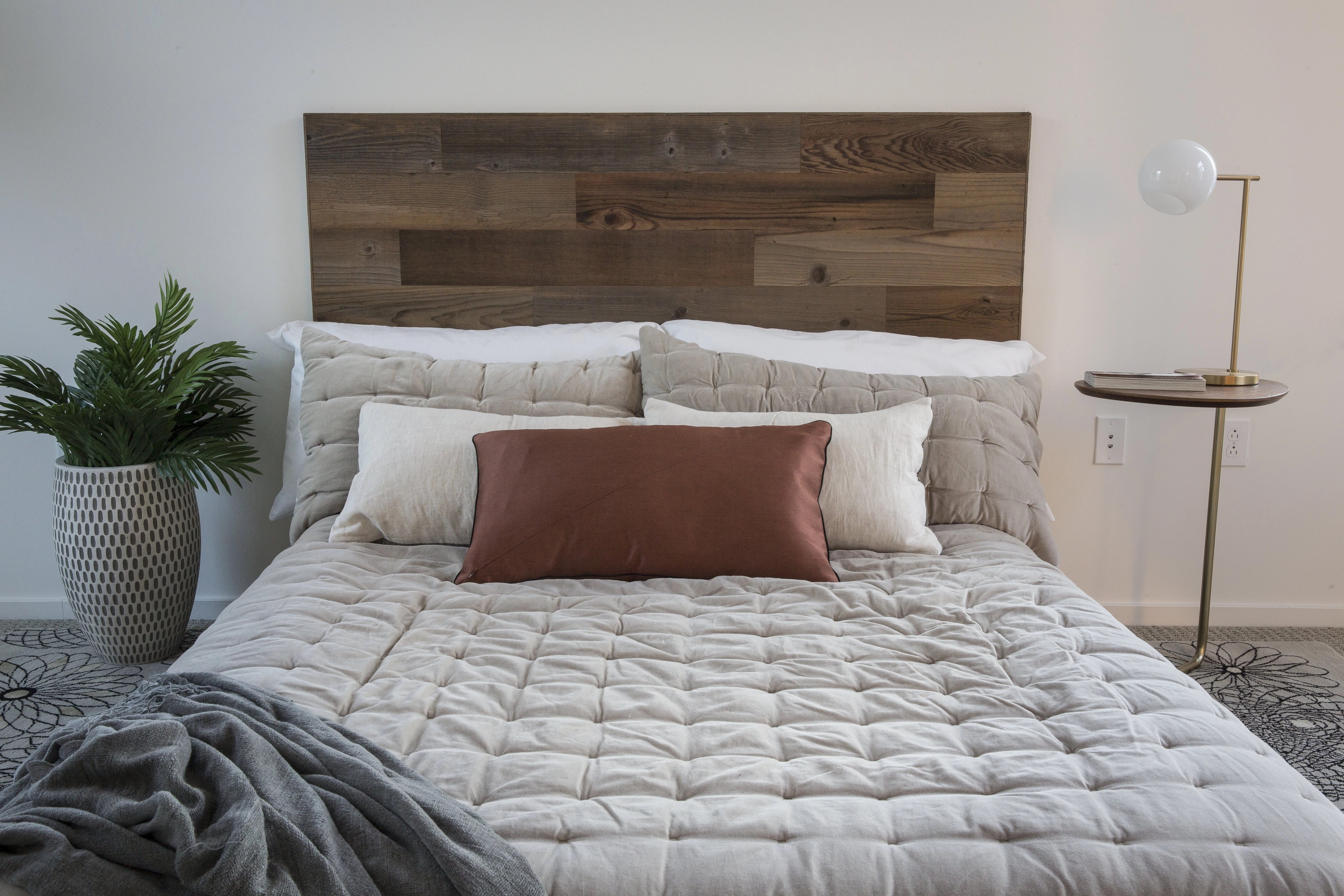 DIY reclaimed wood headboard ont he wall behind a bed, made with real barnwood that comes with a Stikits headboard kit.