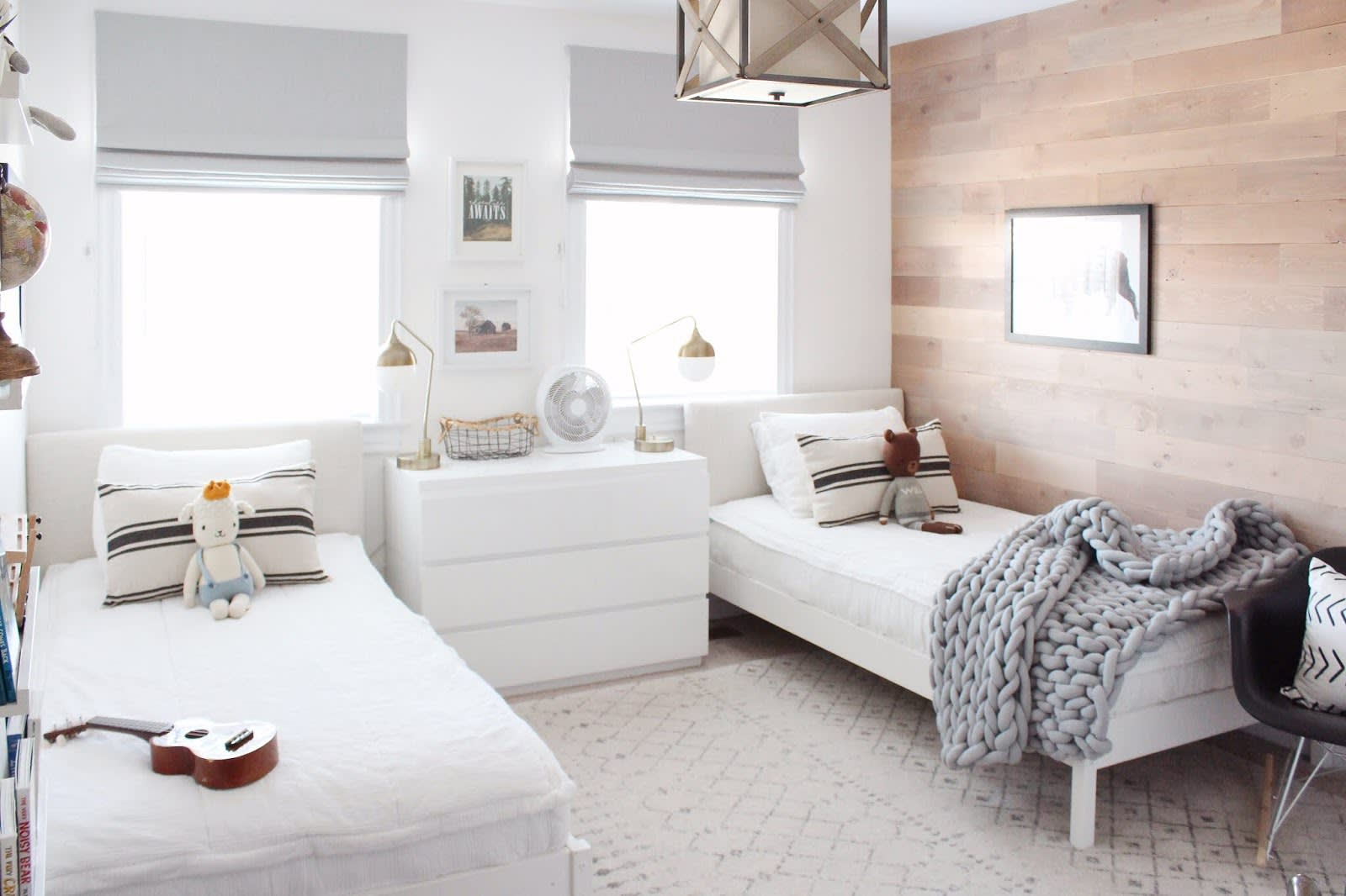 Two twin beds in a light colored boys bedroom with a sand stone colored natural real wood Stikwood accent wall.