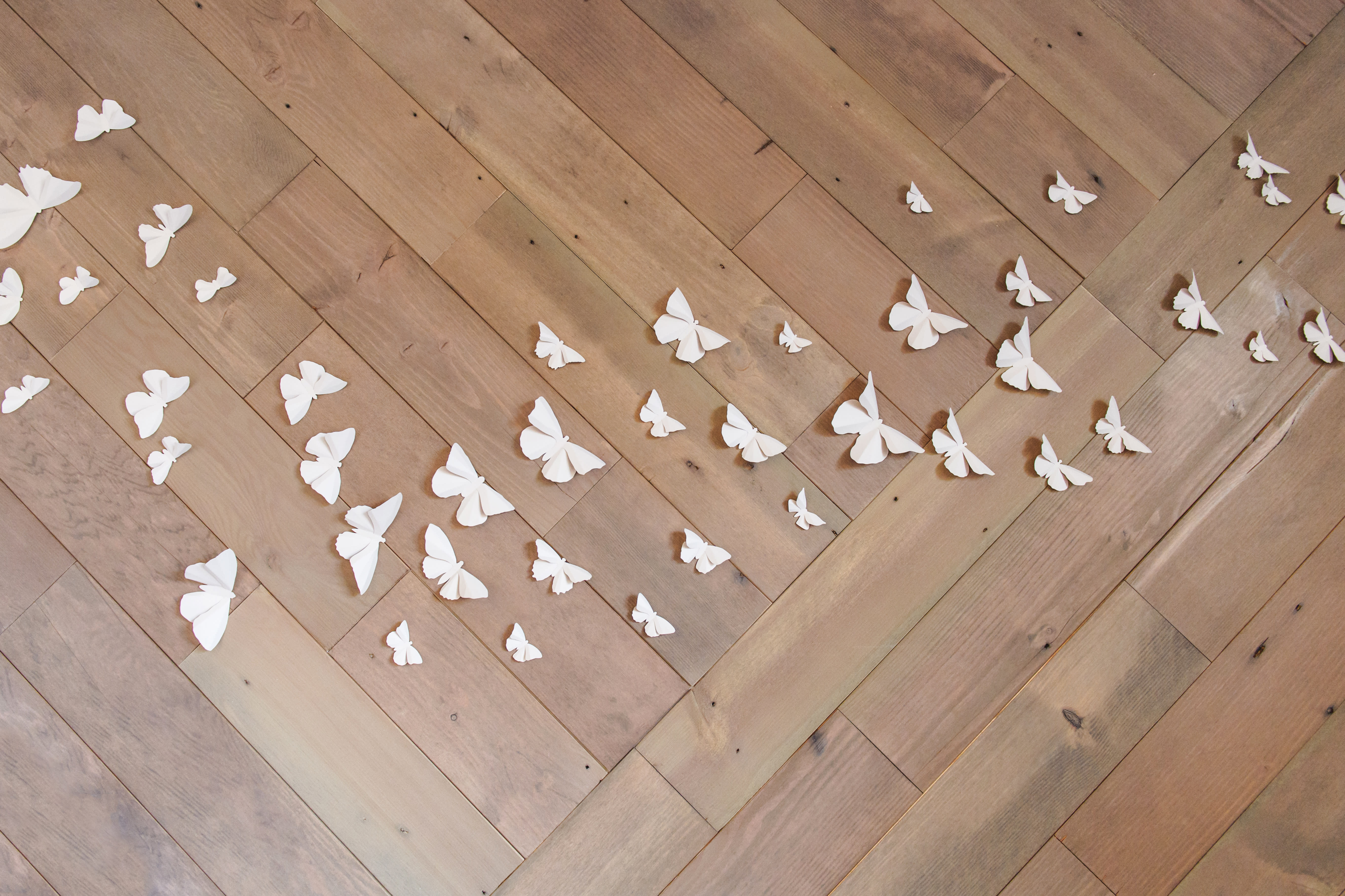 Stikwood peel and stick rustic slate planks set in an angled pattern on a wall in a girls bedroom with 3d white butterflies.