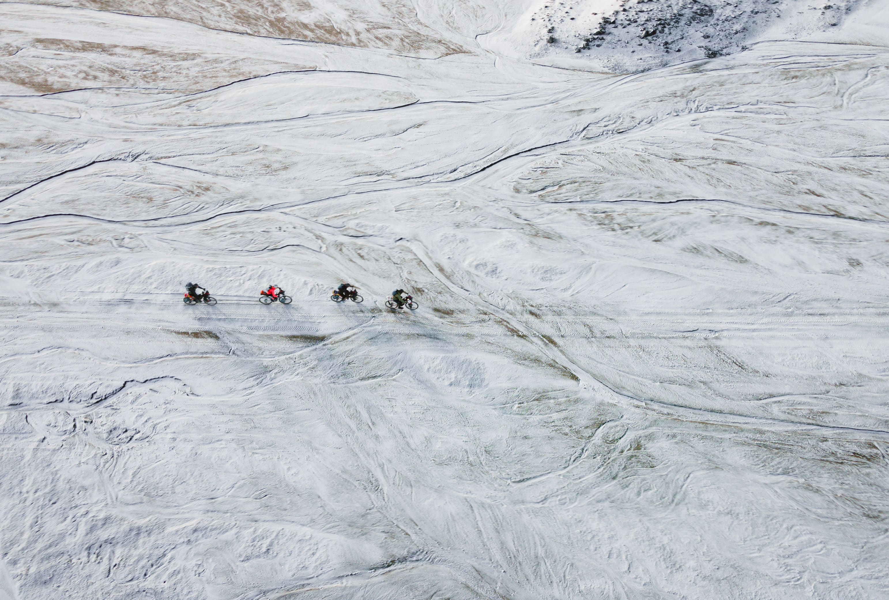 Group riding bikes in icy wilderness