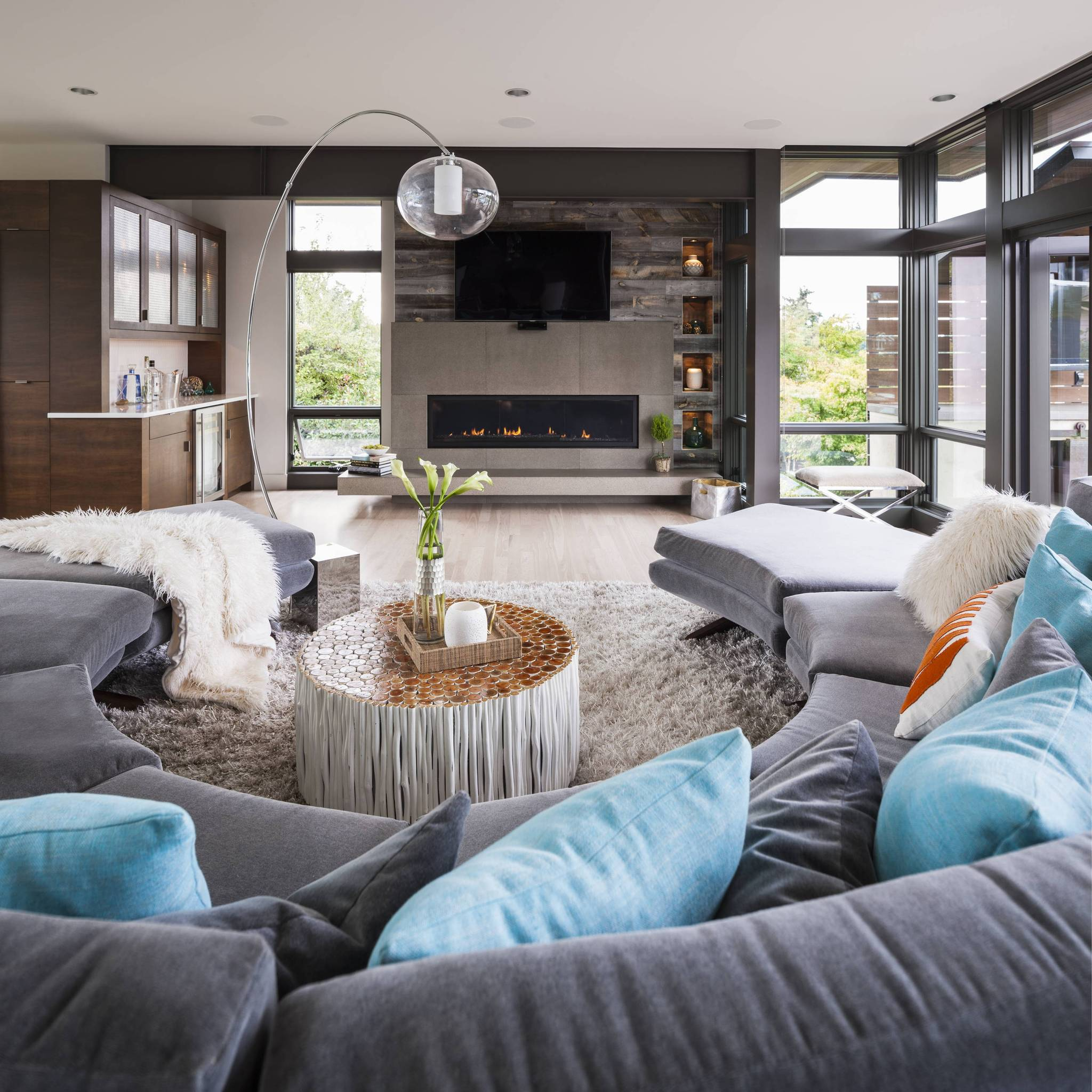 Amazing modern living room design featuring open concept and reclaimed wood feature wall made with peel and stick wood planks.