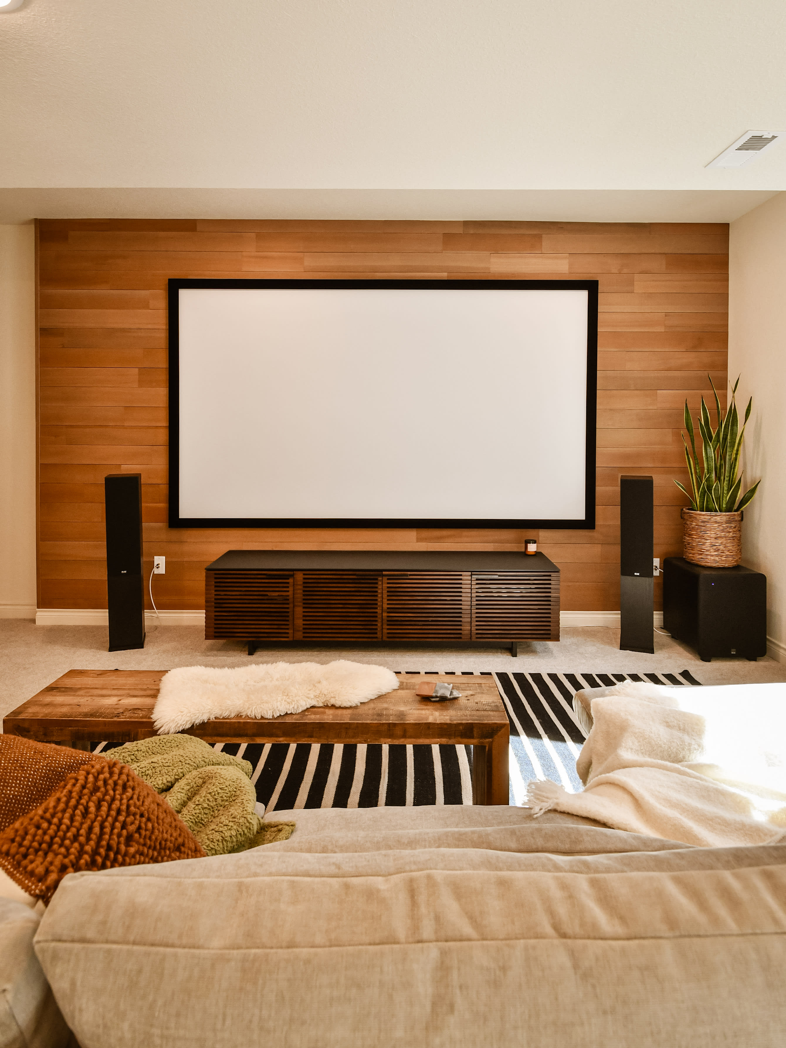 Media room feature wall made with Stikwood peel and stick real wood DIY panels.