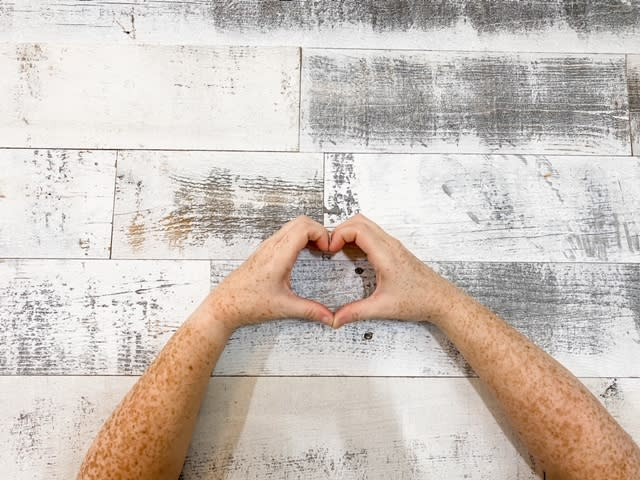 Two hands making a heart shape in from of a Stikwood peel and stick reclaimed weathered wood white accent wall.