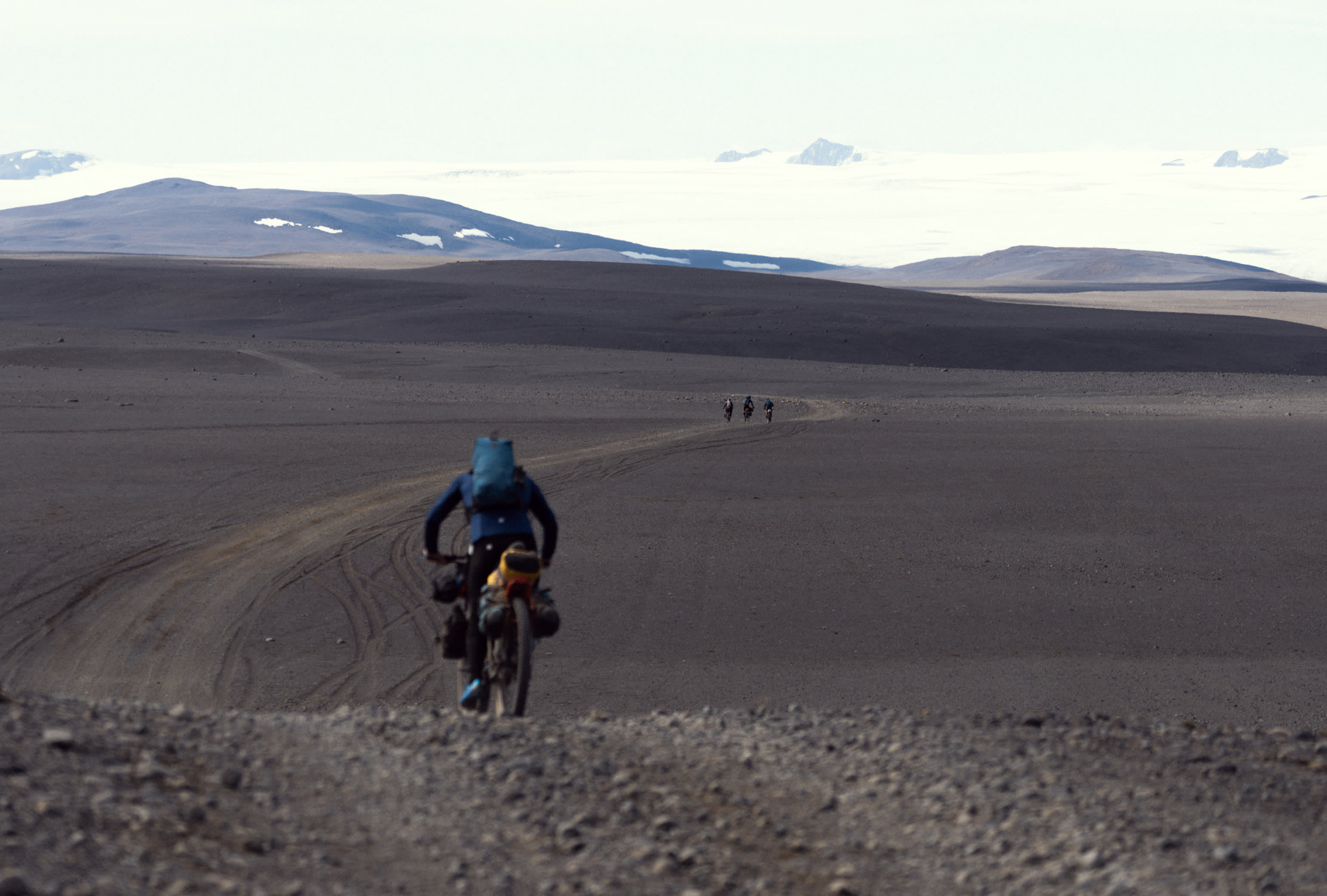 Man riding a bike in wilderness behind a group