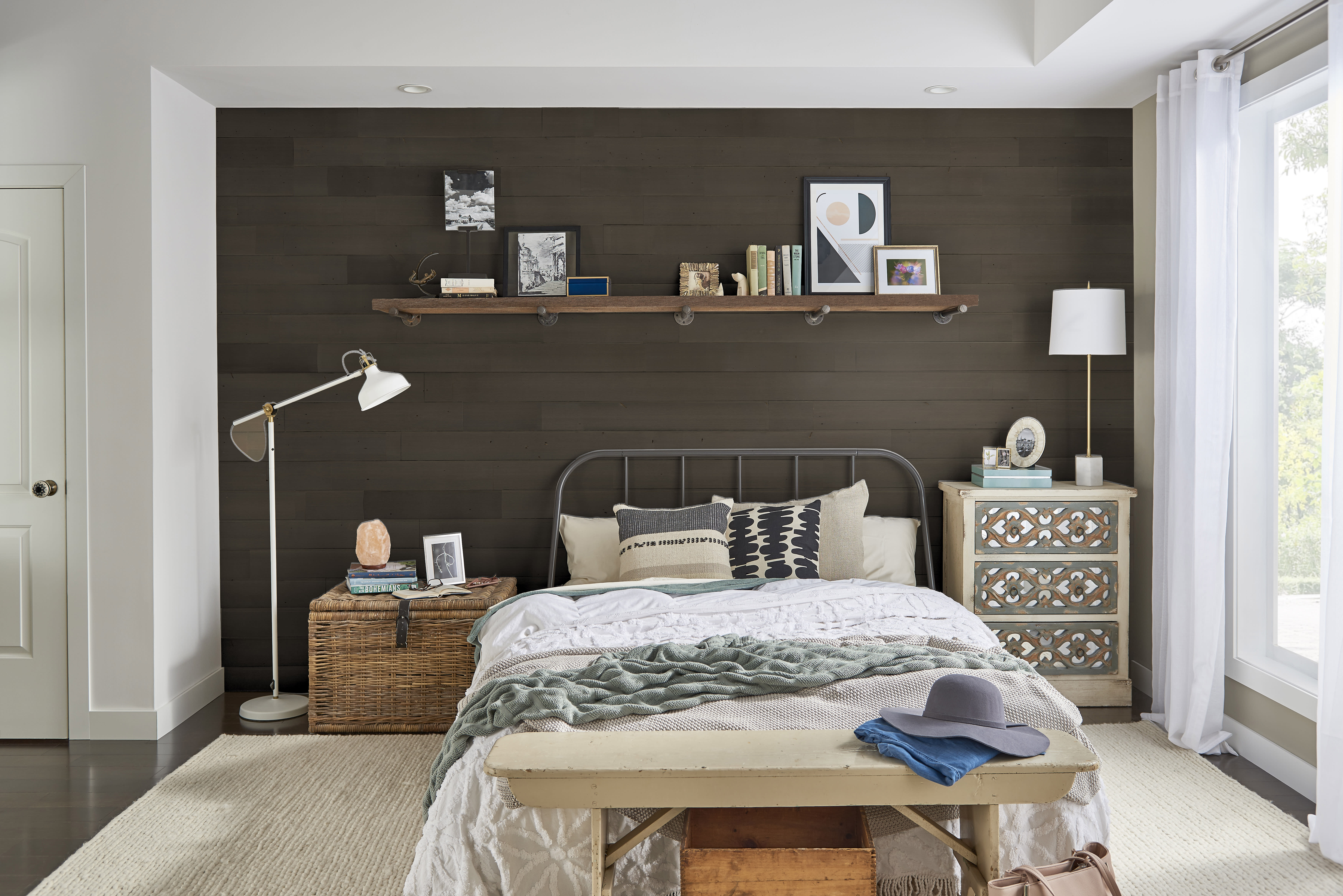 Comfortable bedroom with a dark reclaimed accent wall made from Stikwood peel and stick real wood wall and ceiling planks.