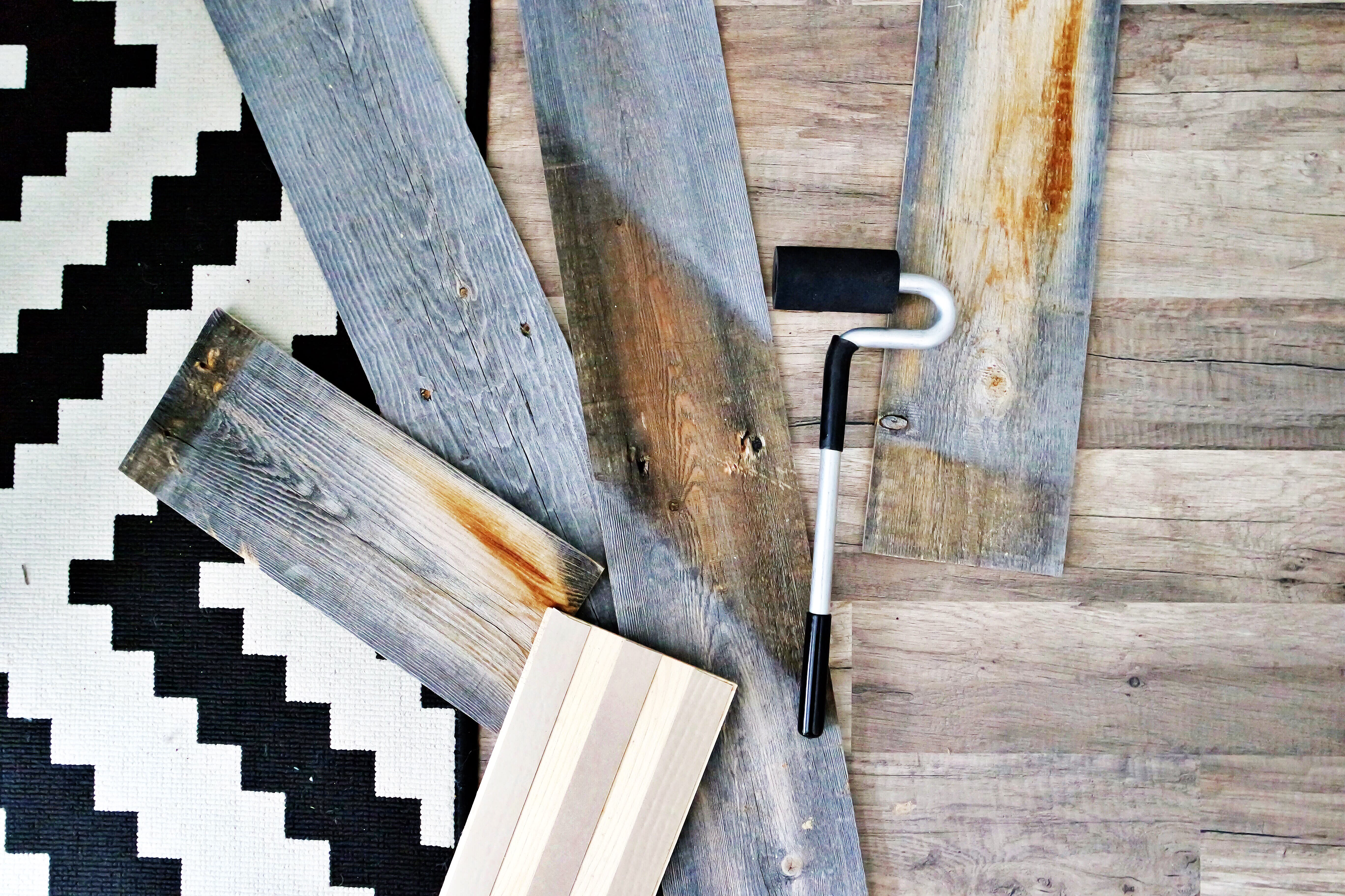 Reclaimed wood planks laying on white and black geometric carpet with other design samples.
