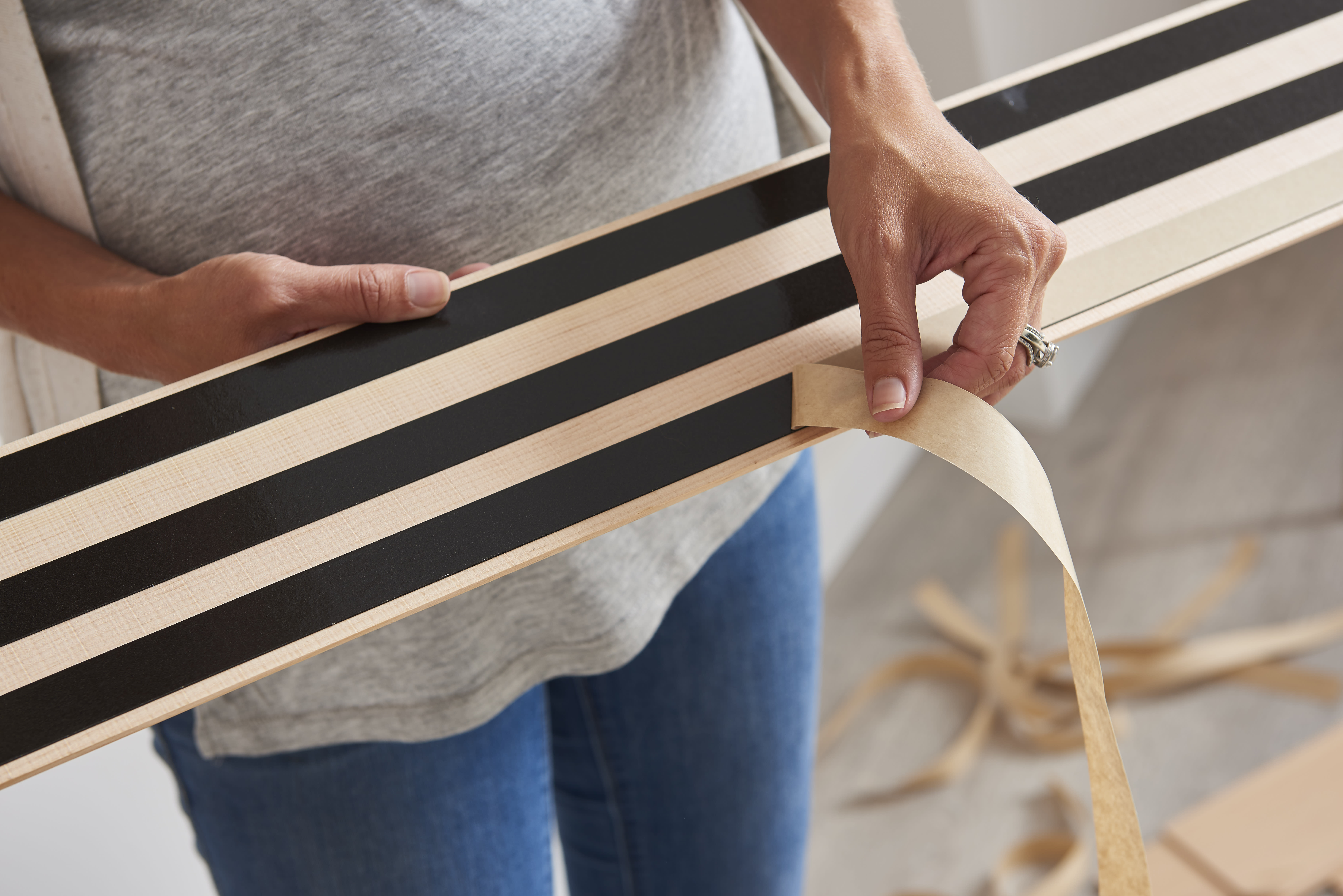 Closeup of a woman peeling the backer off the adhesive strips on the back of a Stikwood real reclaimed wood wall and ceiling plank.