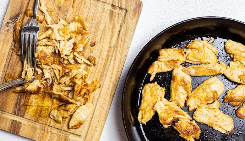 Shredded daring chicken on cutting board