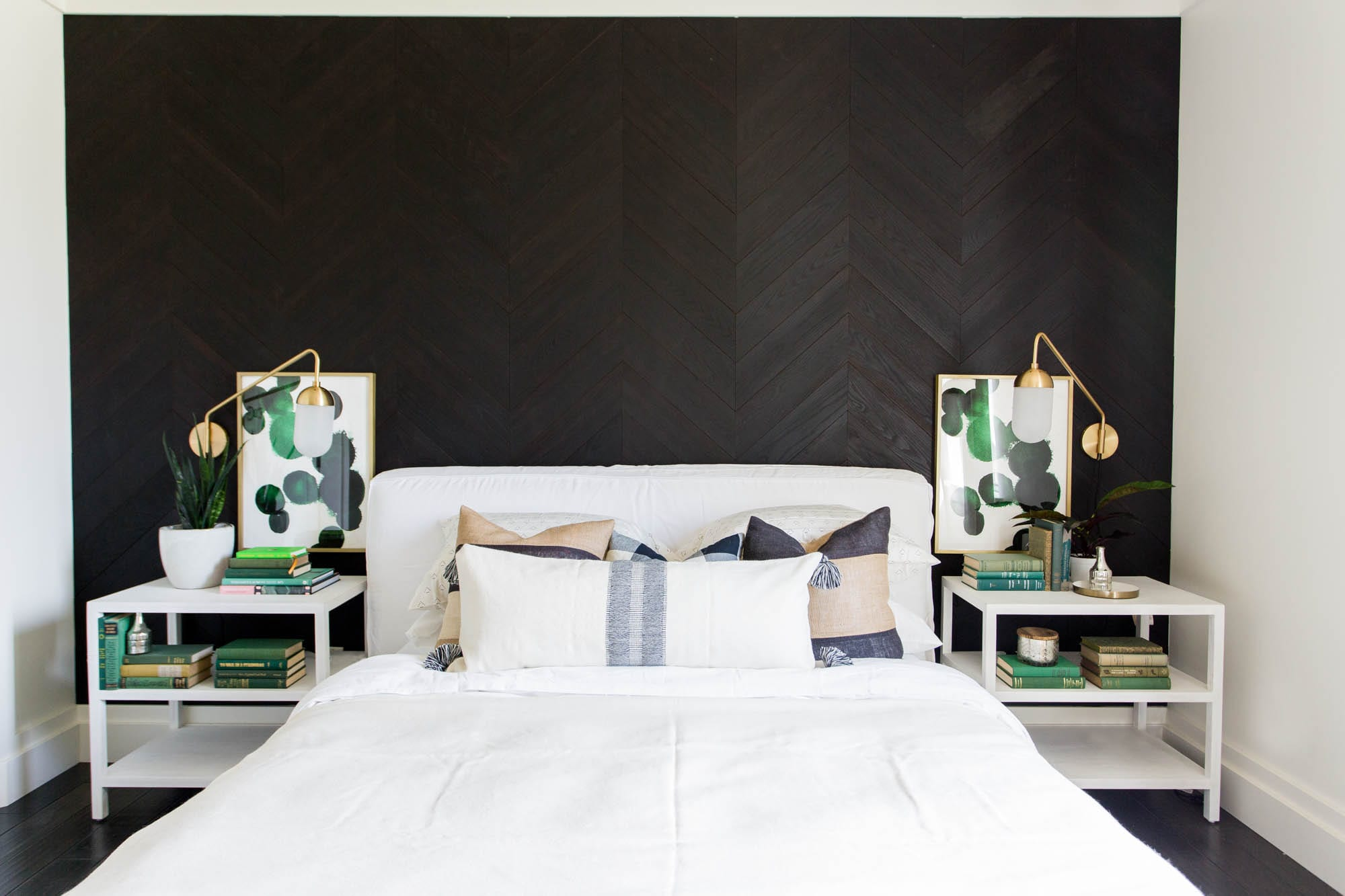 Modern master bedroom with a dark wood plank accent wall in a herringbone pattern made with Stikwood planks.