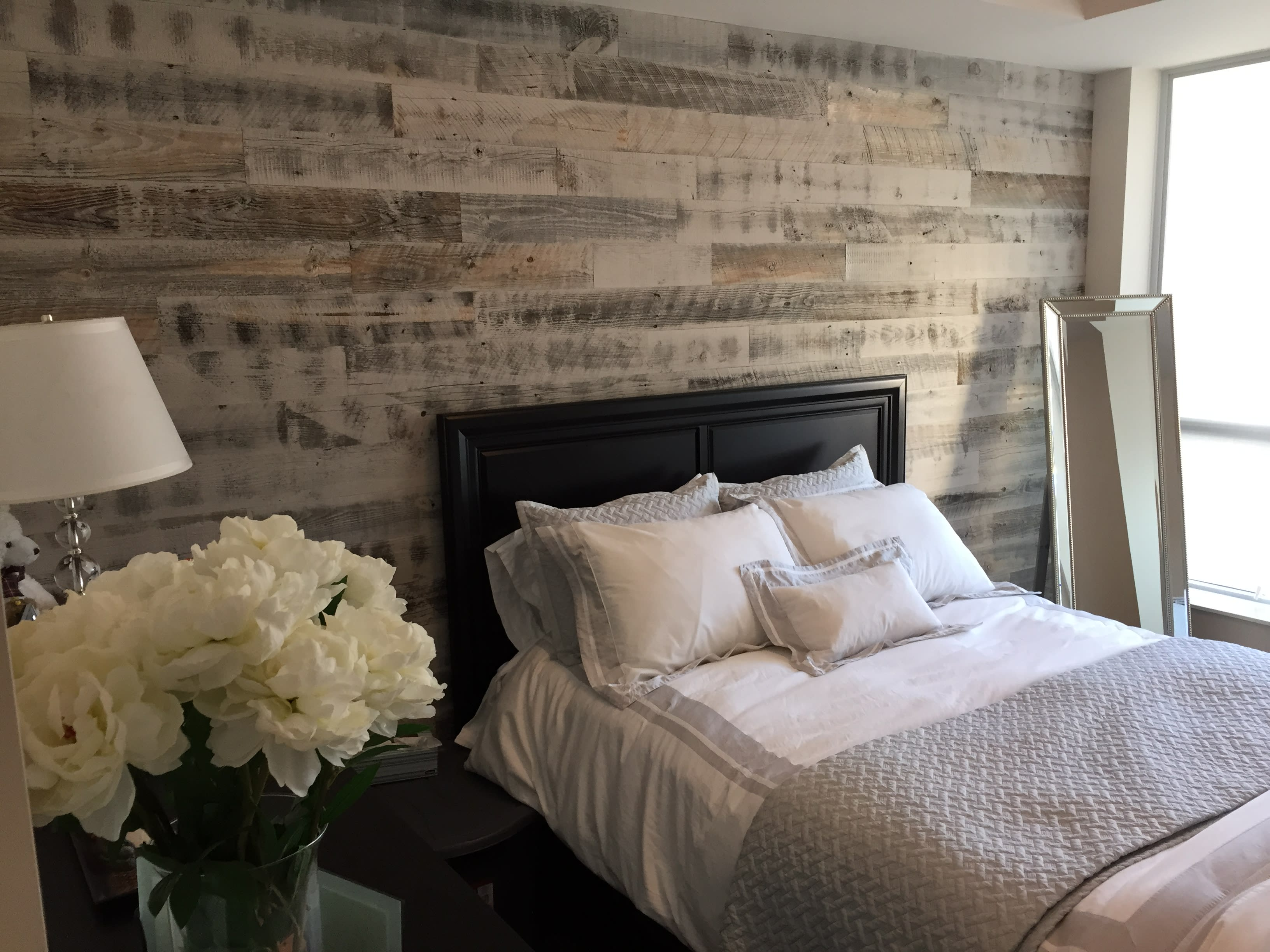 Classic bedroom with a dark wood bed frame and a peel and stick reclaimed gray barnwood accent wall.