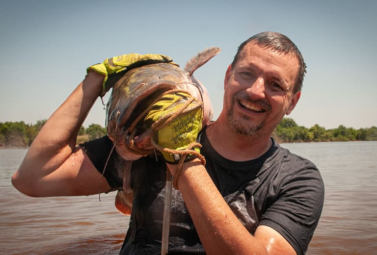 Man standing holding a giant catfish in the water