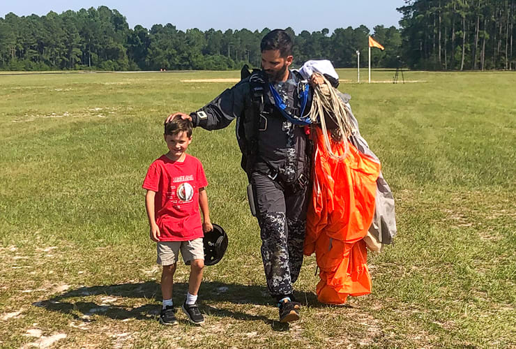 Man carrying parachute with one hand on a little boy's head