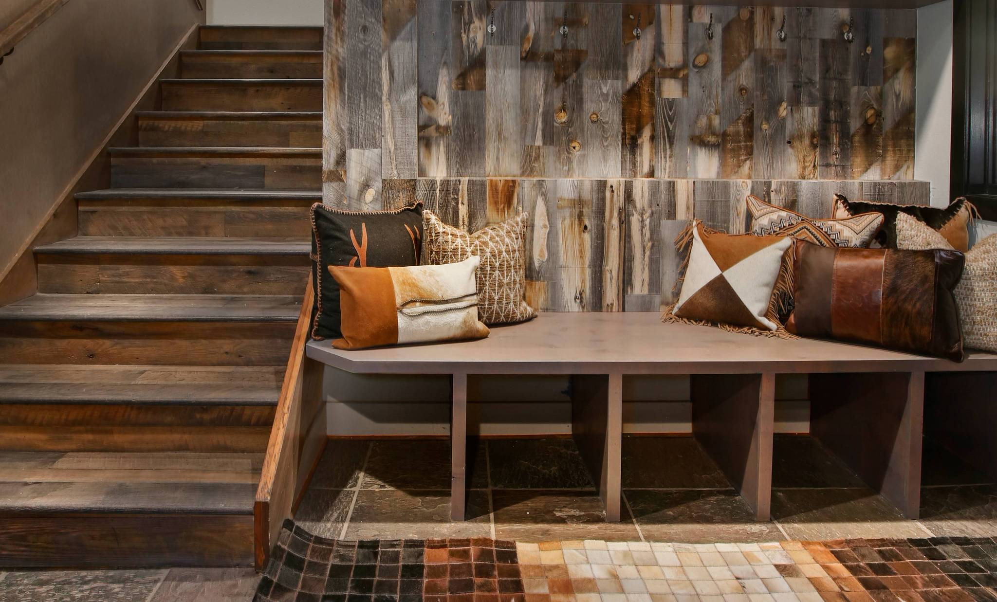 Rustic cabin entryway with shoe shelves accented by Stikwood peel and stick reclaimed weathered wood wall and ceiling planks.