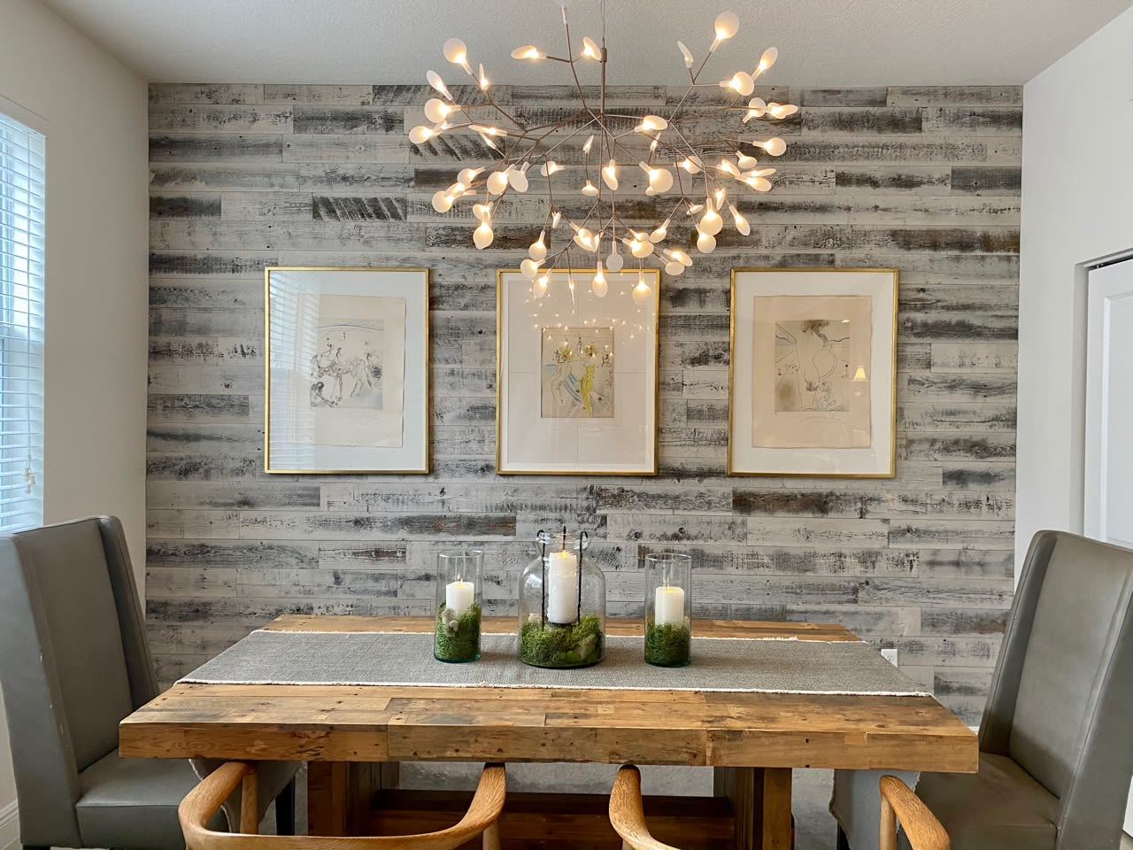 Modern farmhouse dining room with reclaimed wood table and a Stikwood peel and stick reclaimed plank weathered wood accent wall.