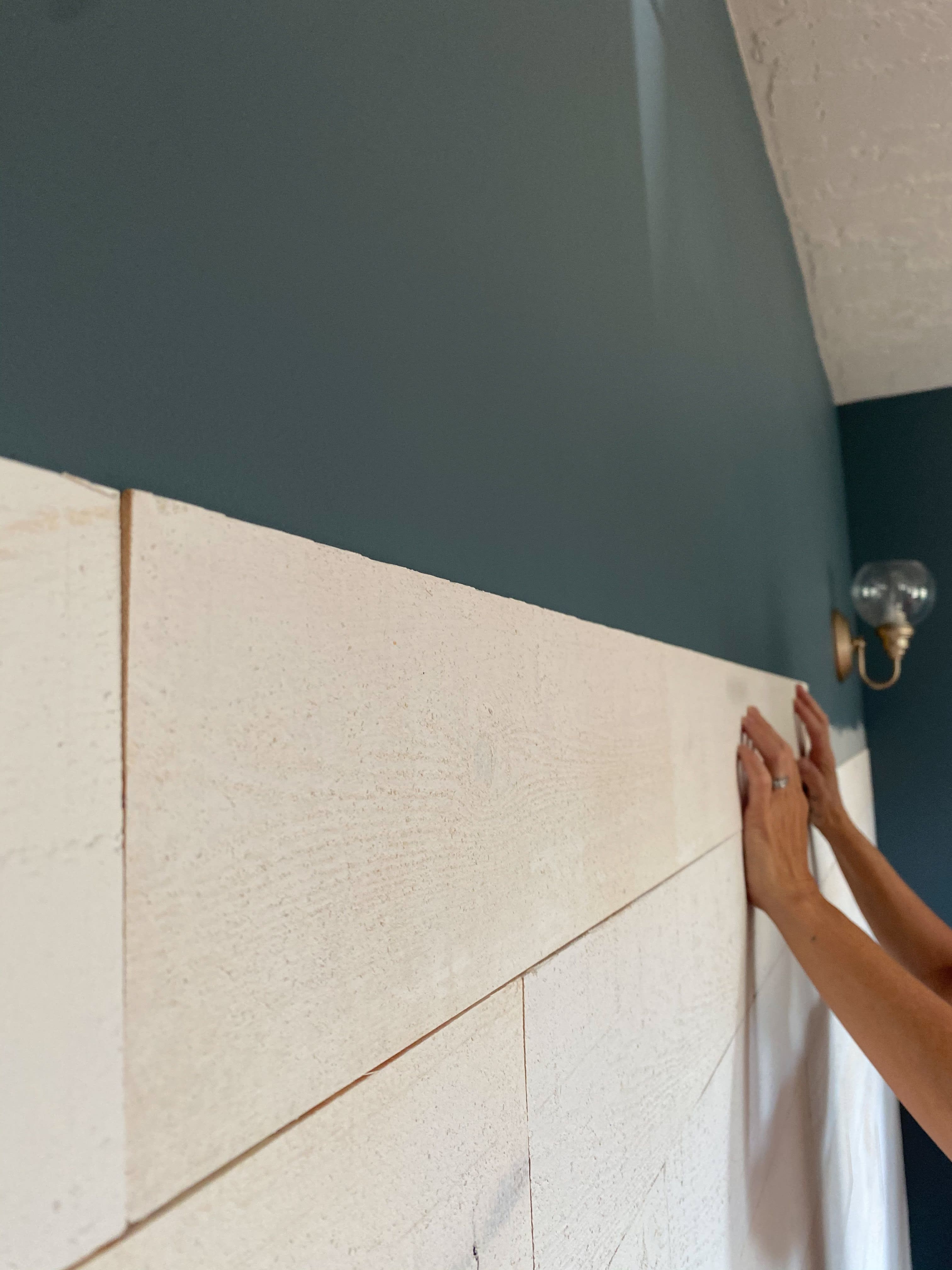 Hands placing a stikwood peel and stick Hamptons shiplap plank on a green painted wall.