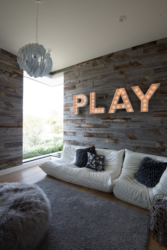 Modern rustic living room with wall to wall reclaimed weathered wood barnwood planks and large illuminated play words on the wall.