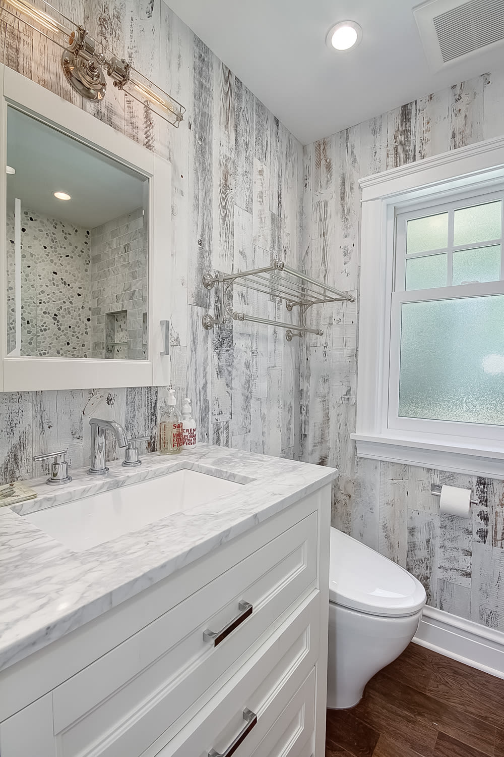 Bathroom accent wall and backsplash created using Stikwood peel and stick reclaimed weathered wood white wood planks.