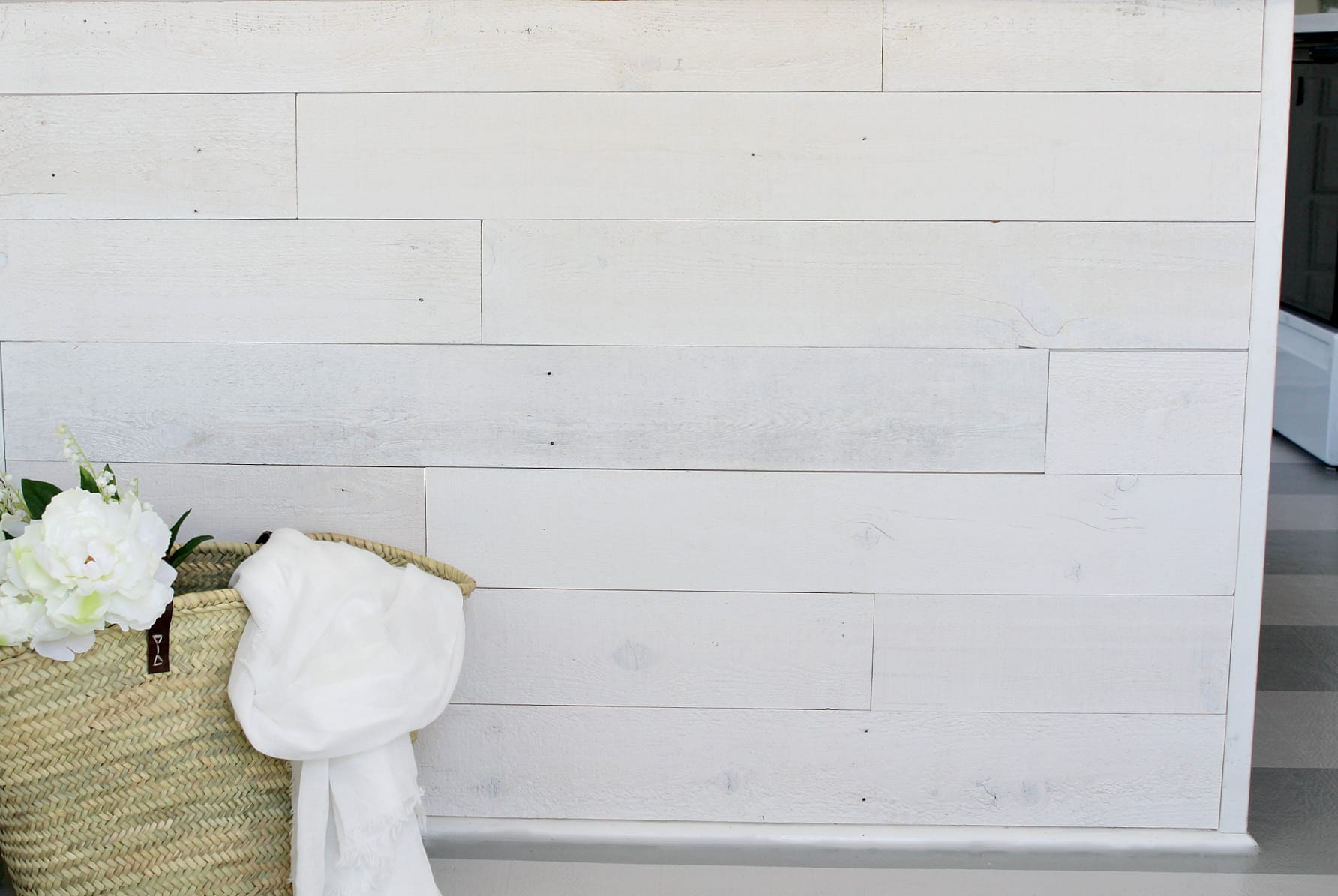 Close up of a shiplap wall created using Stikwood Hamptons finish peel and stick reclaimed wood wall and ceiling planks.
