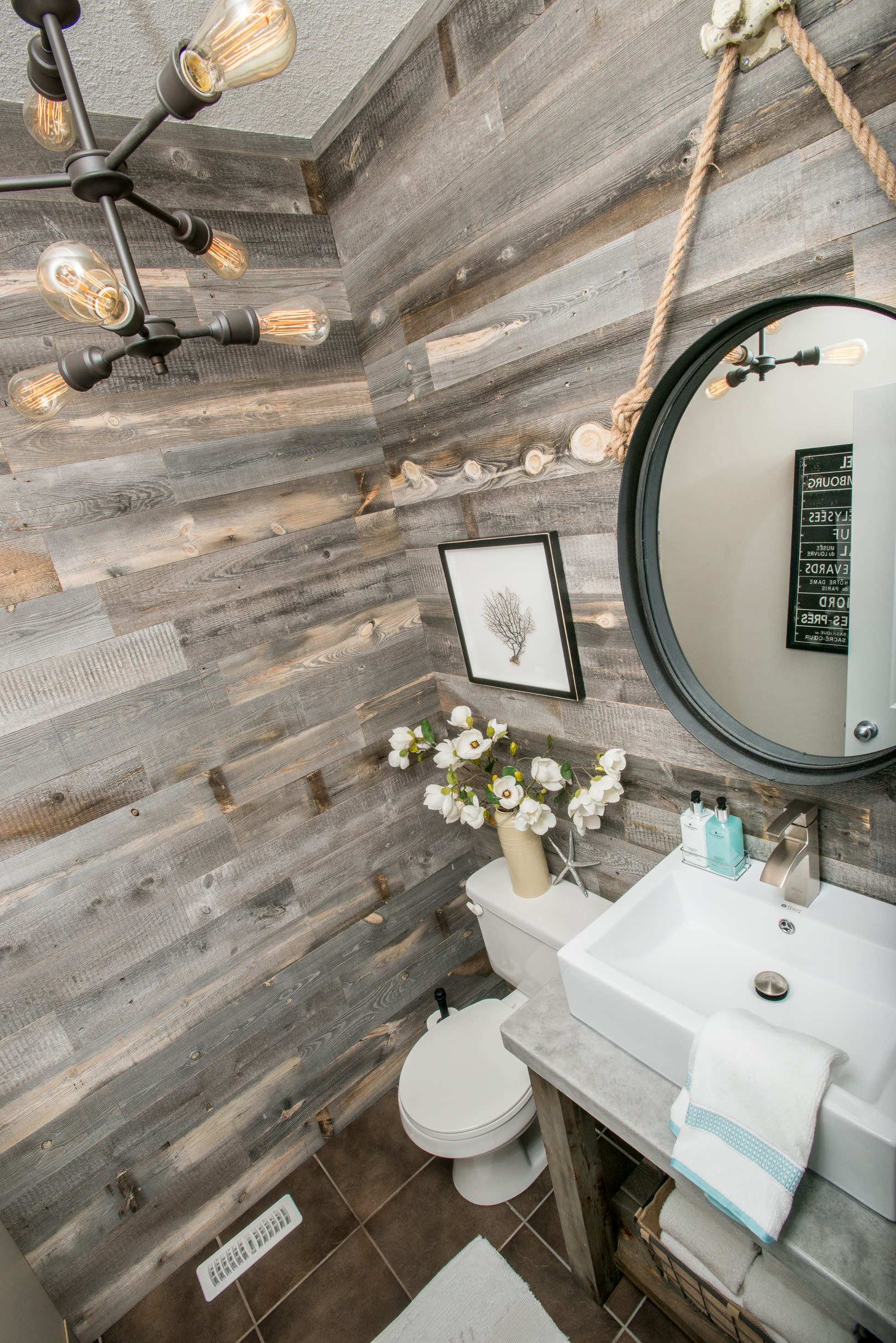 Reclaimed barnwood accent walls made with Stikwood peel and stick reclaimed wood planks in a bathroom angled shot.