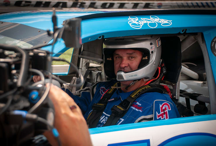 Man sitting inside a stock car, hands on the wheel