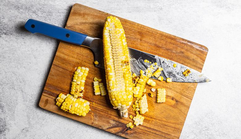Cut corn on a cutting board with knife