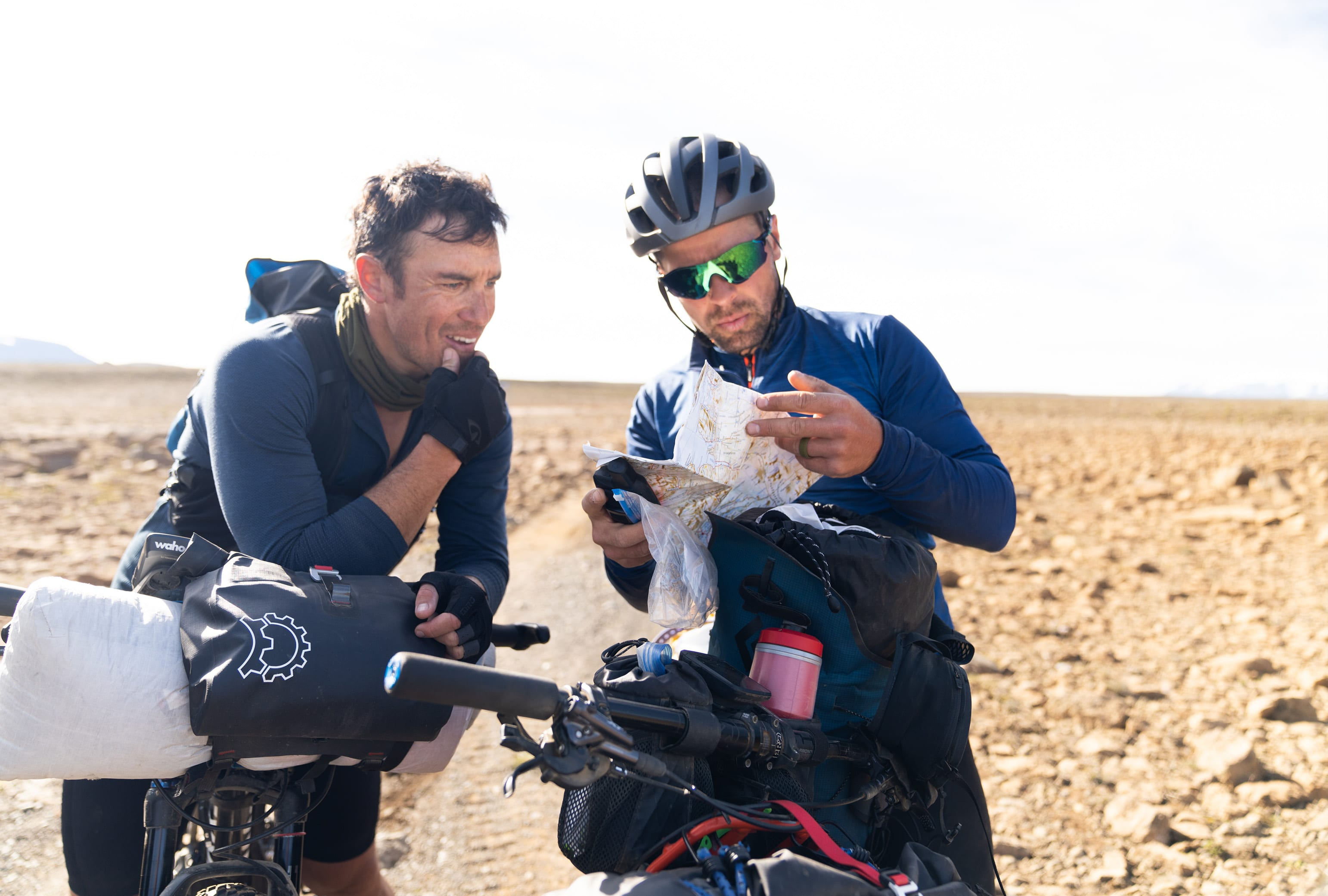 Two men looking at a map while sitting on their bikes