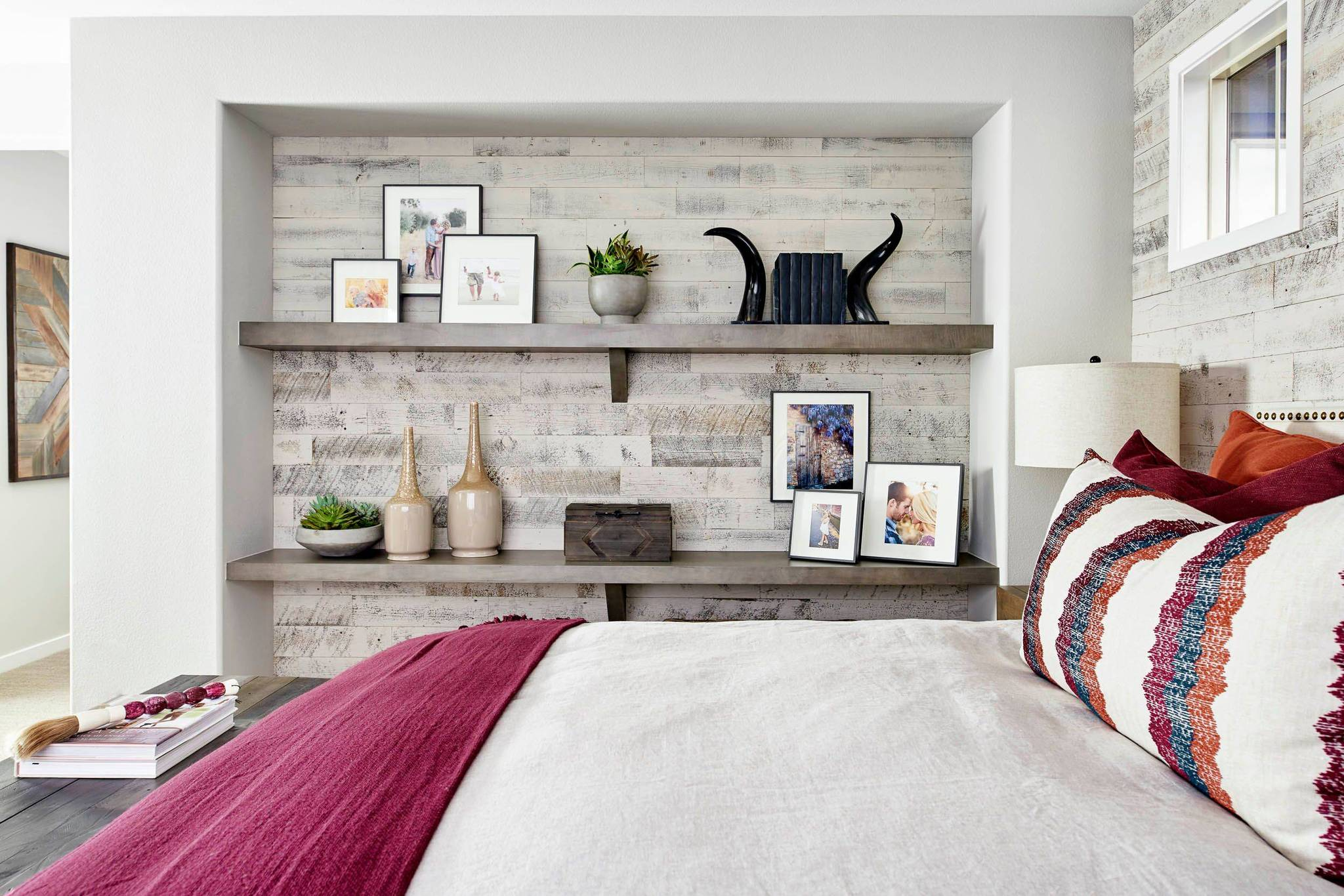 White classic bedroom with inset wall with shelves backed by real reclaimed wood to create a dramatic focal point.