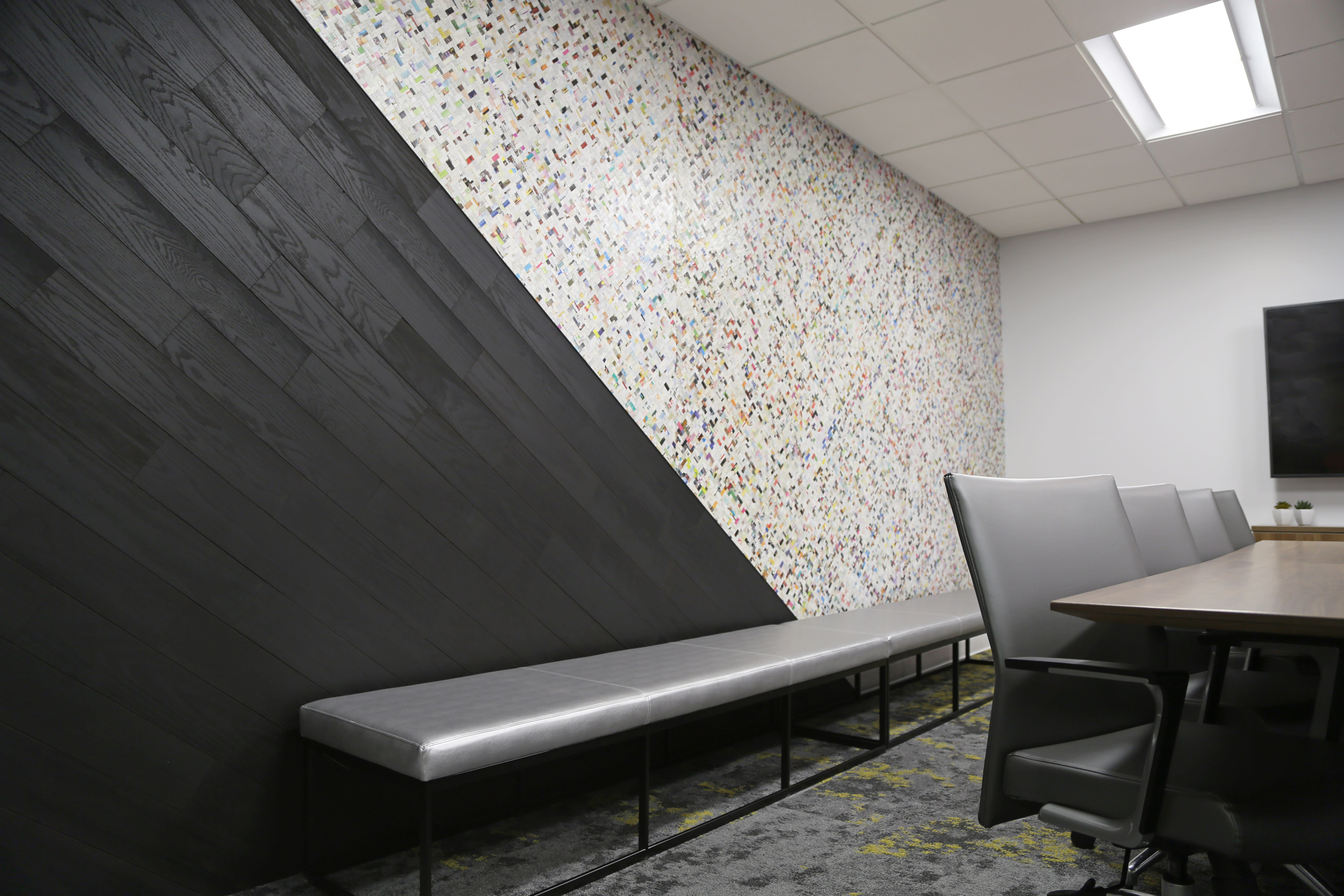 Modern office lobby with a angled install of Charcoal colored peel and stik wood planks.