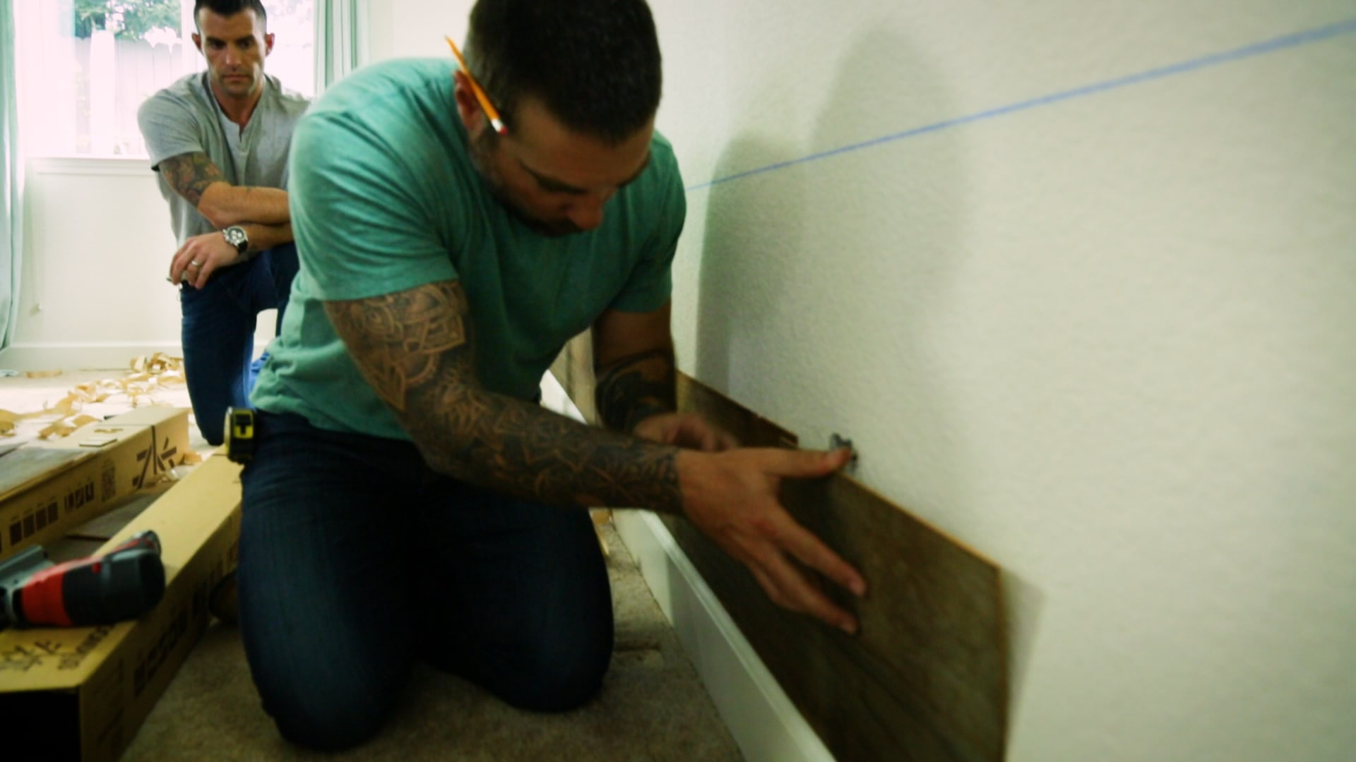 The cousins demonstrating how to install peel and stick wood wall planks in a master bedroom.
