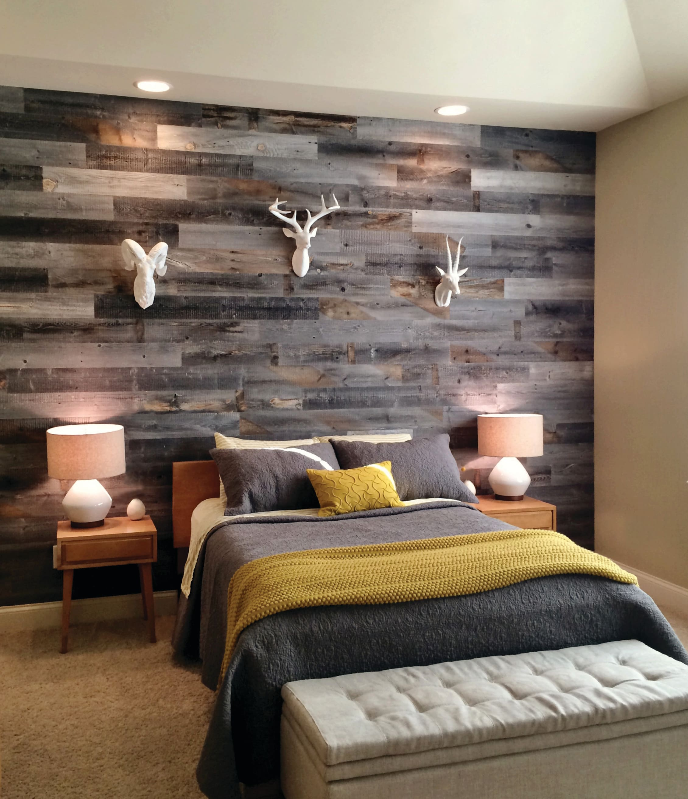 Modern rustic bedroom with a low bed in front of a reclaimed barnwood wood panel accent wall made with Stikwood.