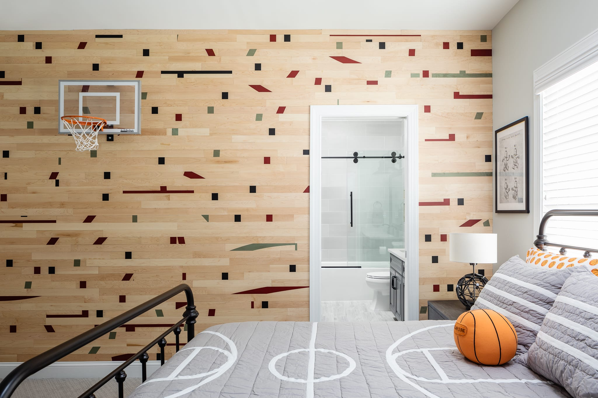 Kids basketball theme room by Grace Thomas Design with hoop on a wall covered with Fanwall real maple peel and stick planks with custom printed basketball court markings in an abstract pattern.