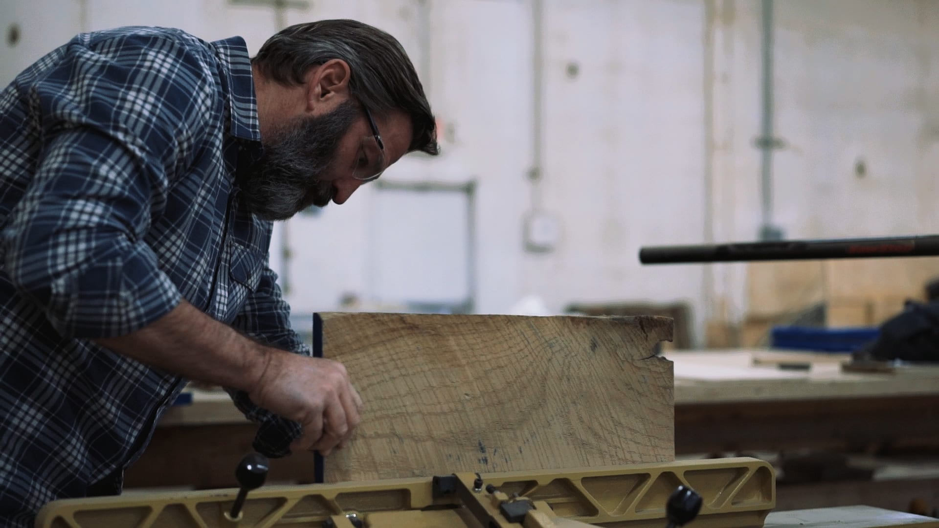 Jerry McCall, the creator of Stikwood peel and stick wood planks, cutting reclaimed wood on a table saw.