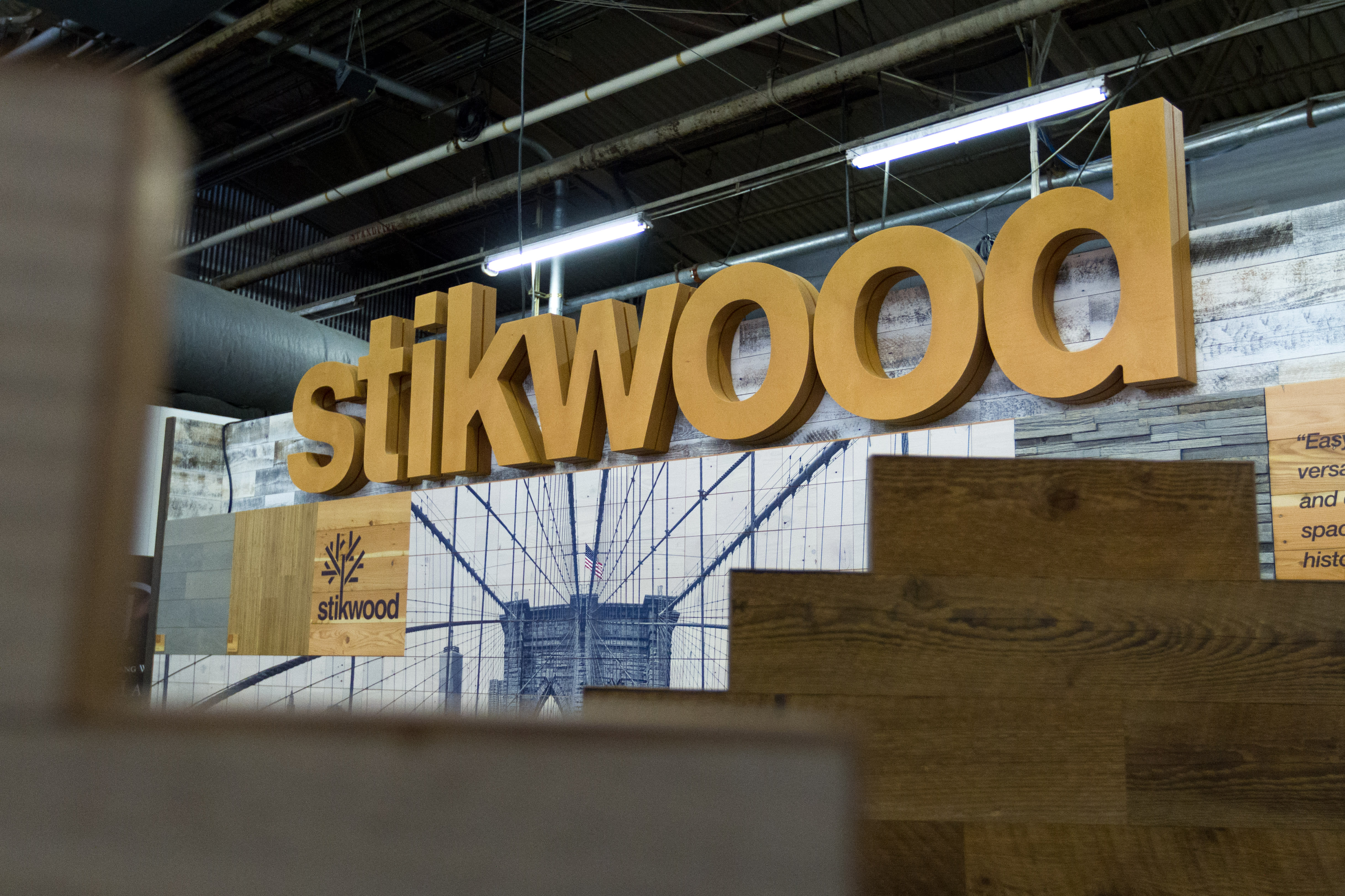 Stikwood NYC tradeshow booth showing assembles brooklyn bridge peel and stick wood collage.