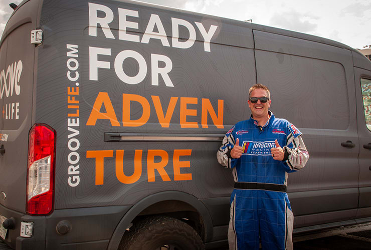 """Man standing next to a van reading """"Ready for Adventure"""""""