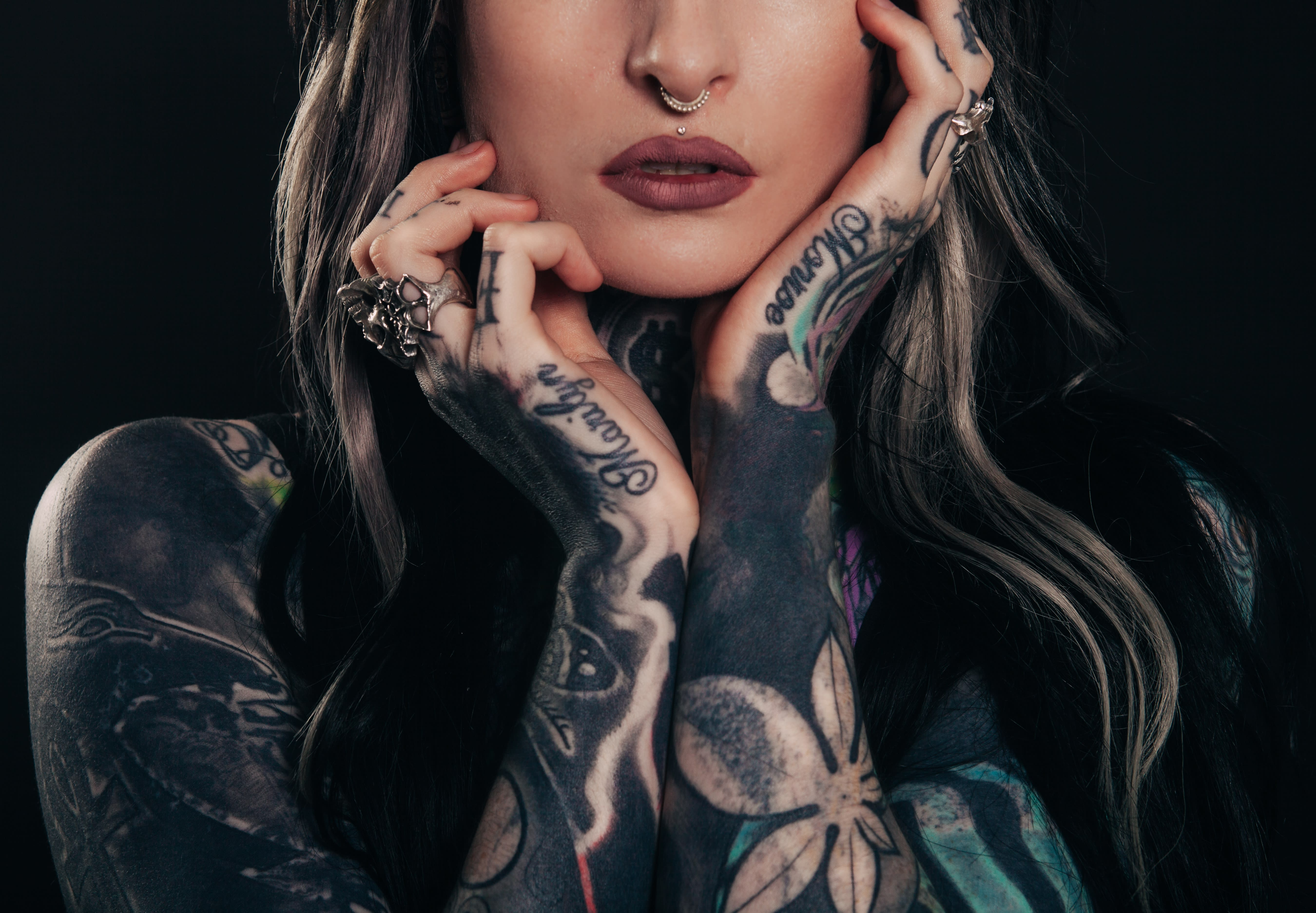 Tattoo'd Girl with hands on chin.