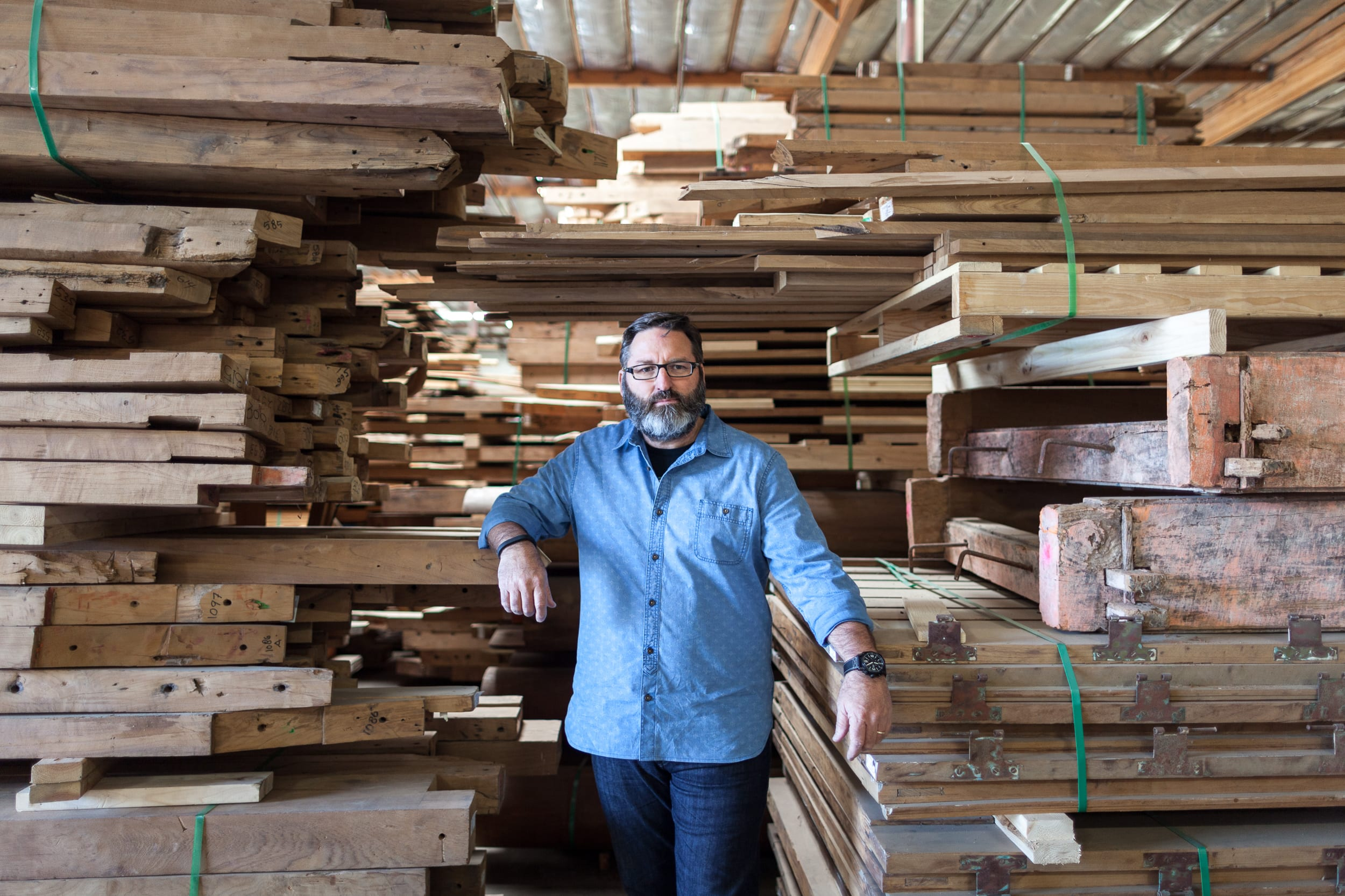 Stikwood inventor, Jerry McCall, standing next to stacks of real reclaimed wood that will become Stikwood peel and stick wood wall and ceiling planks.