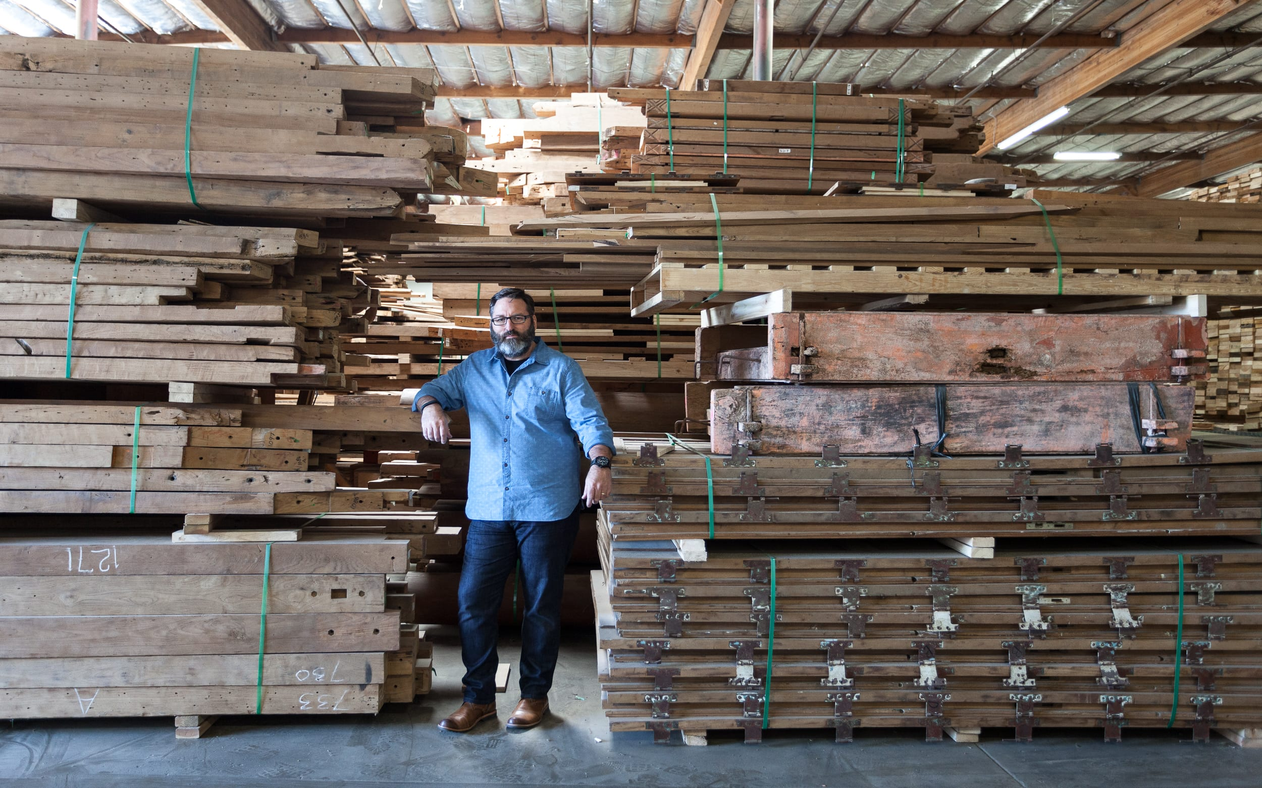 Large stacks of reclaimed wood boards and beams with master woodworker standing between.