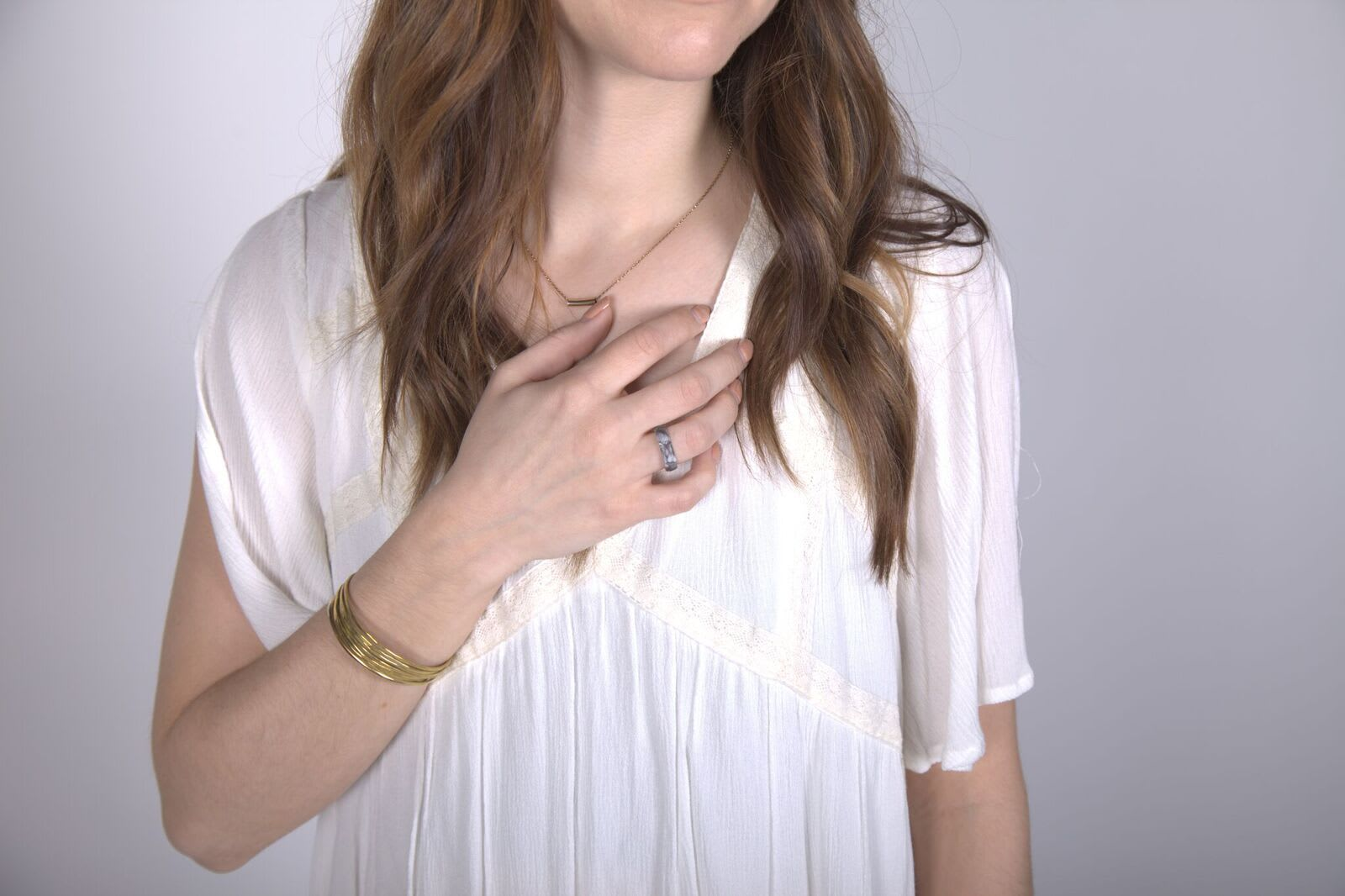 woman holding her hand to her heart with a ring on