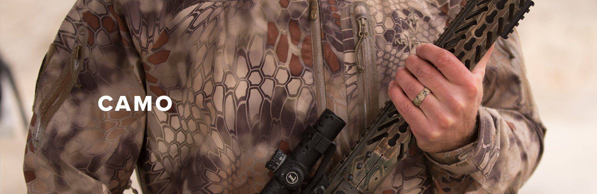 Camo, man holding a large rifle in kryptek camouflage