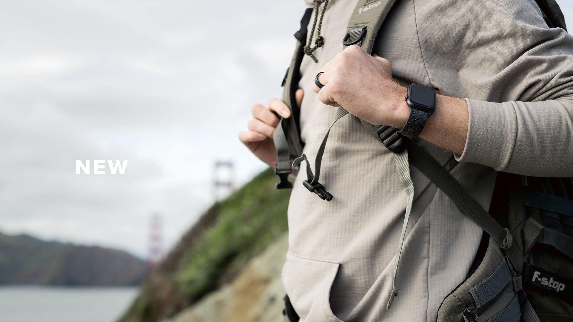 New, a man with a ring and black watch band holds on to his backpacks straps with a bridge in the background